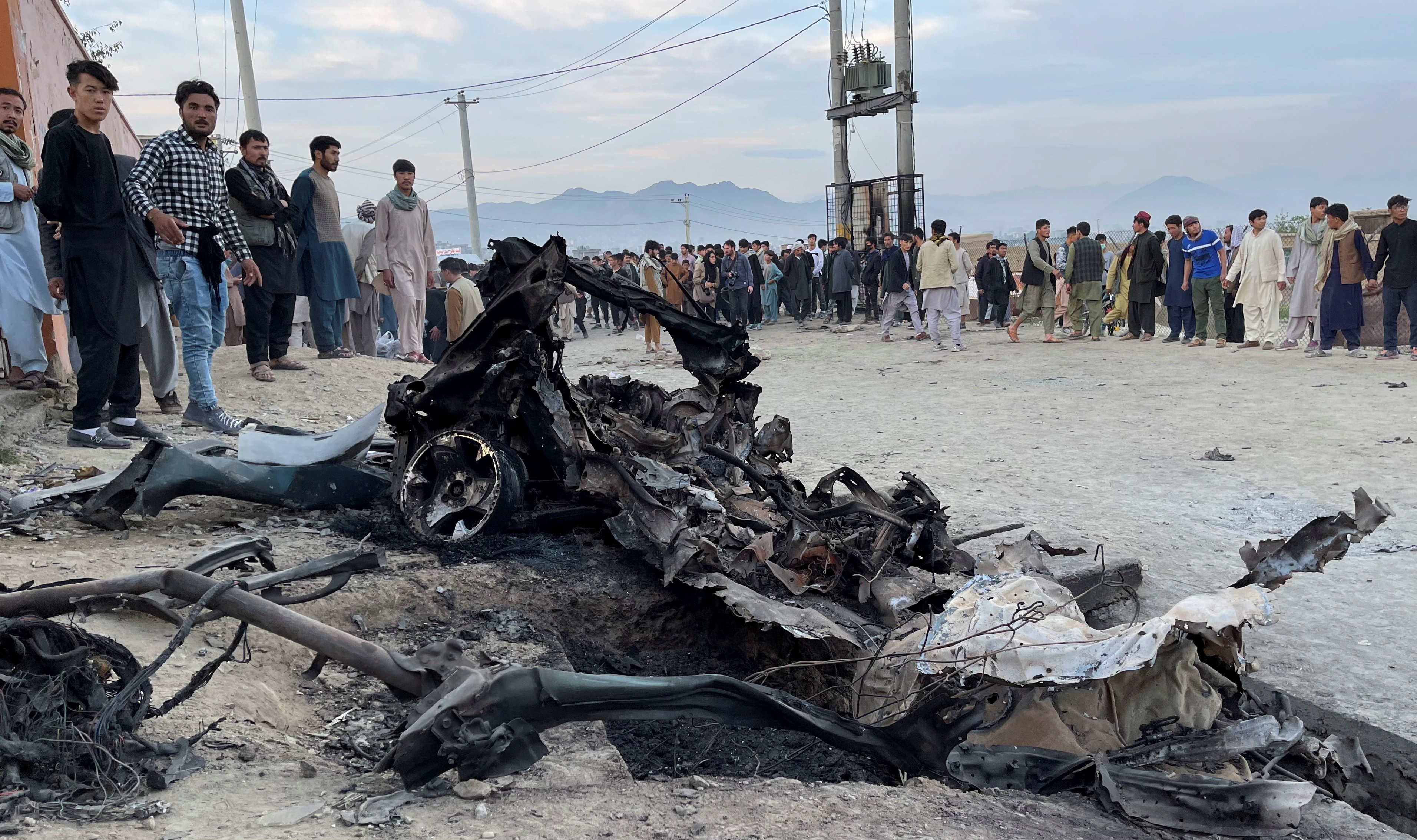 People stand at the site of a blast in Kabul, Afghanistan May 8, 2021.  REUTERS/Stringer