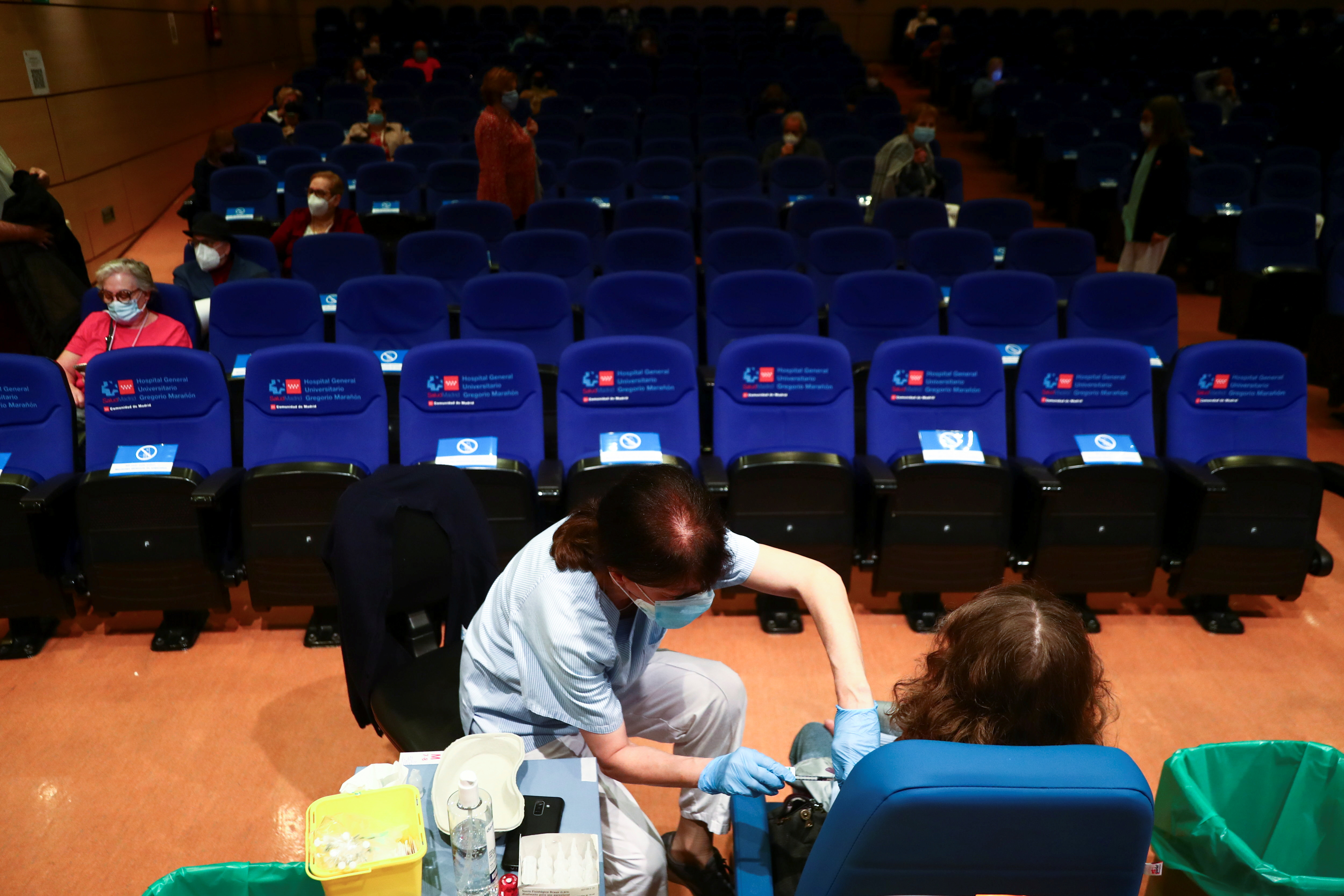 A woman, between 70 and 74 years old, receives her first dose of the Pfizer/BioNTech coronavirus disease (COVID-19) vaccine, as the outbreak continues, in a conference hall at Gregorio Maranon hospital in Madrid, Spain, April 13, 2021. REUTERS/Sergio Perez