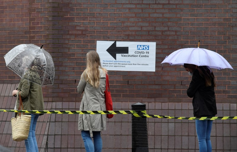 People queue in the rain to receive a COVID-19 vaccination amid the spread of the coronavirus disease pandemic, London, Britain, June 18, 2021. REUTERS/Toby Melville