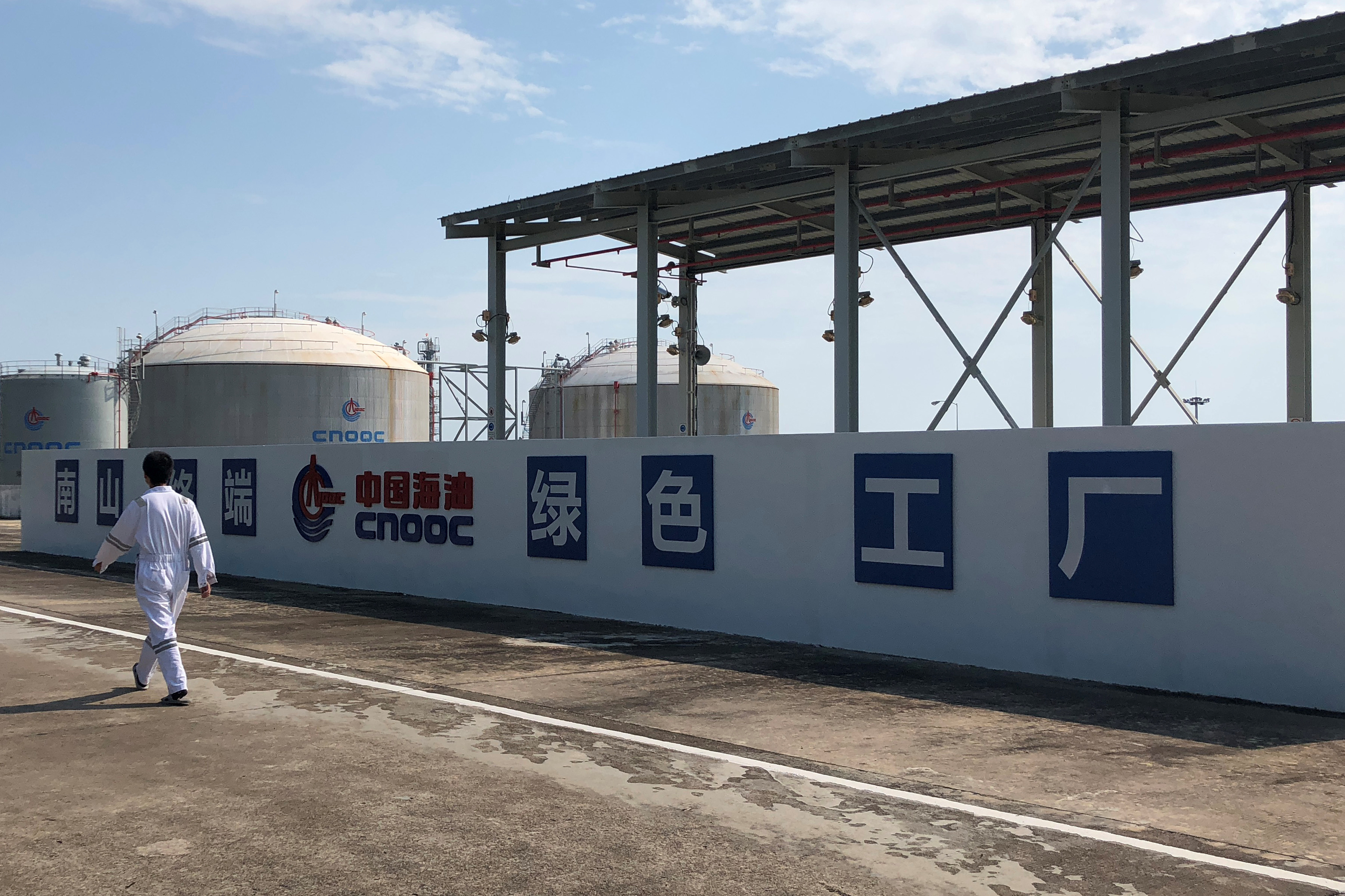 A worker walks past the logo of China National Offshore Oil Corporation (CNOOC) at its Nanshan liquefied natural gas (LNG) terminal in Hainan province, China September 24, 2019.  REUTERS/Muyu Xu
