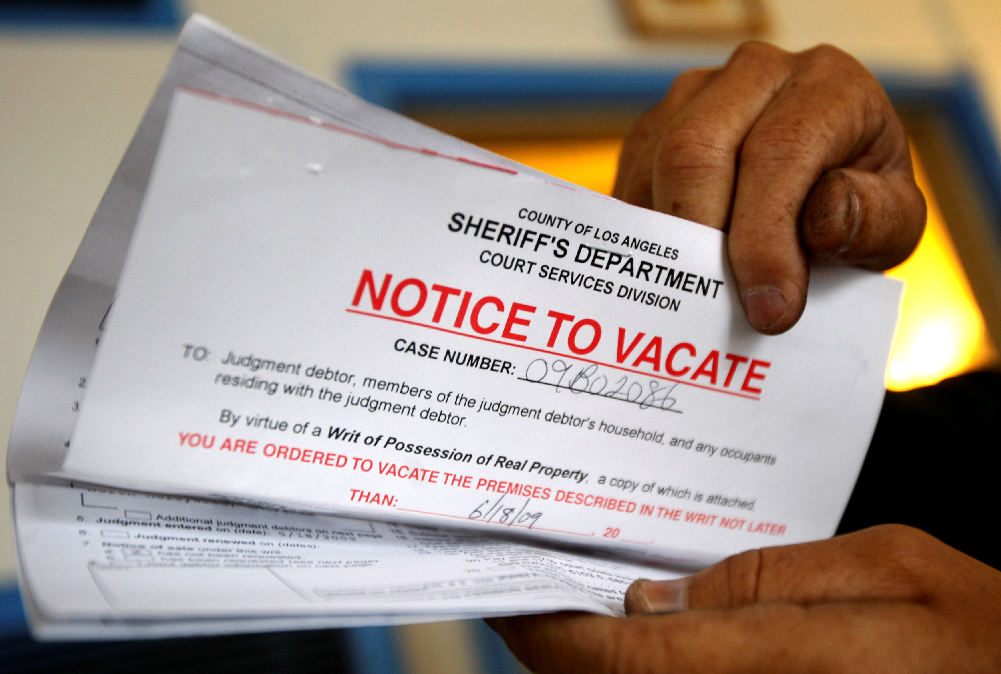 Vicente Oliveros holds up his eviction notice in Los Angeles, June 11, 2009.    REUTERS/Lucy Nicholson//File Photo