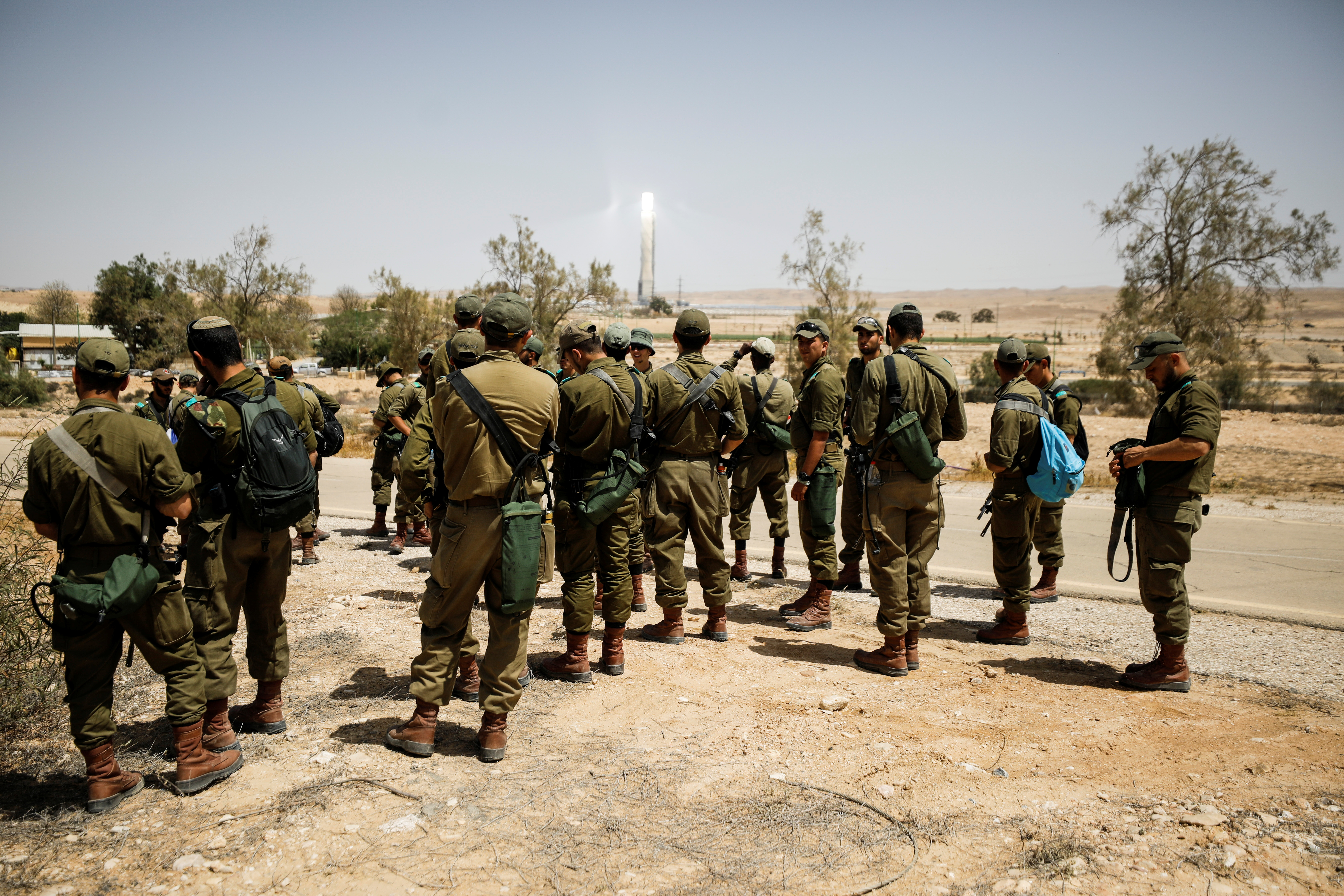 Israeli soldiers gather as they survey the area after a Syrian missile exploded in southern Israel, the Israeli military said, in Ashalim, southern Israel April 22, 2021. REUTERS/Amir Cohen