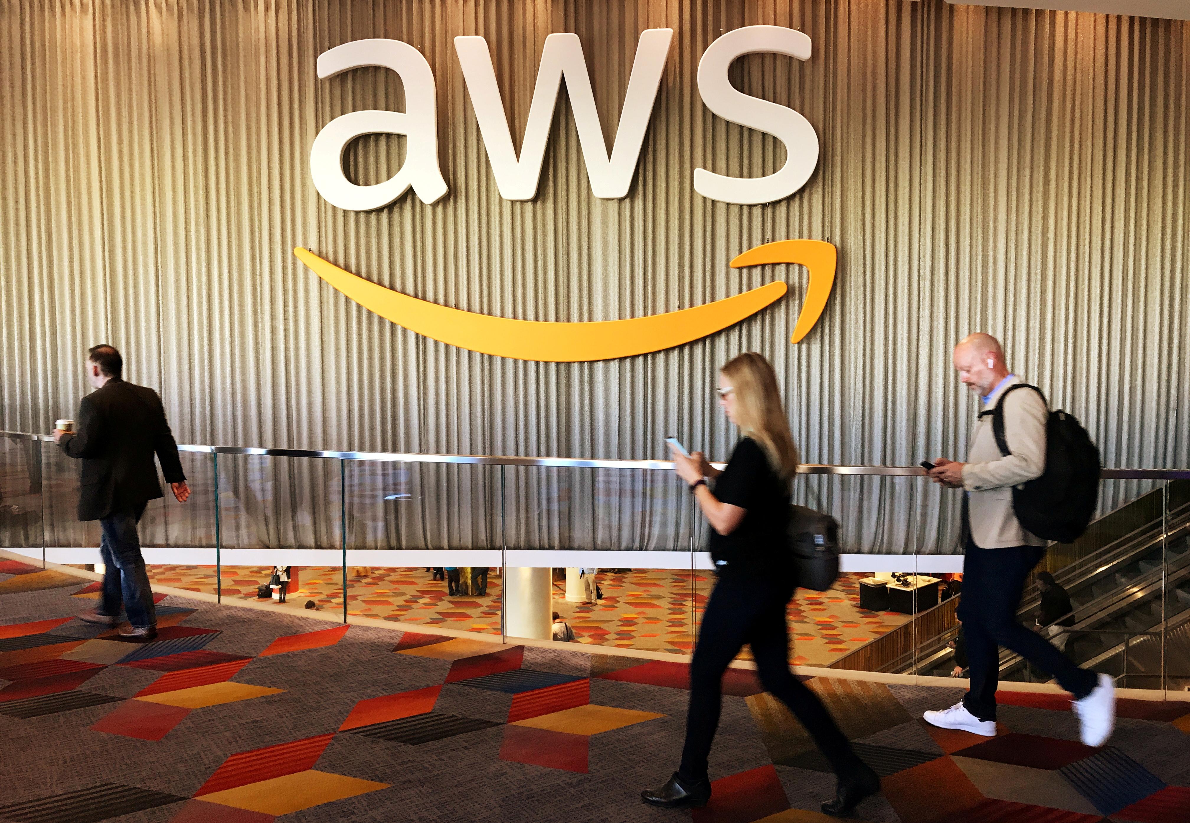 Attendees at Amazon.com Inc annual cloud computing conference walk past the Amazon Web Services logo in Las Vegas, Nevada, U.S., November 30, 2017. REUTERS/Salvador Rodriguez