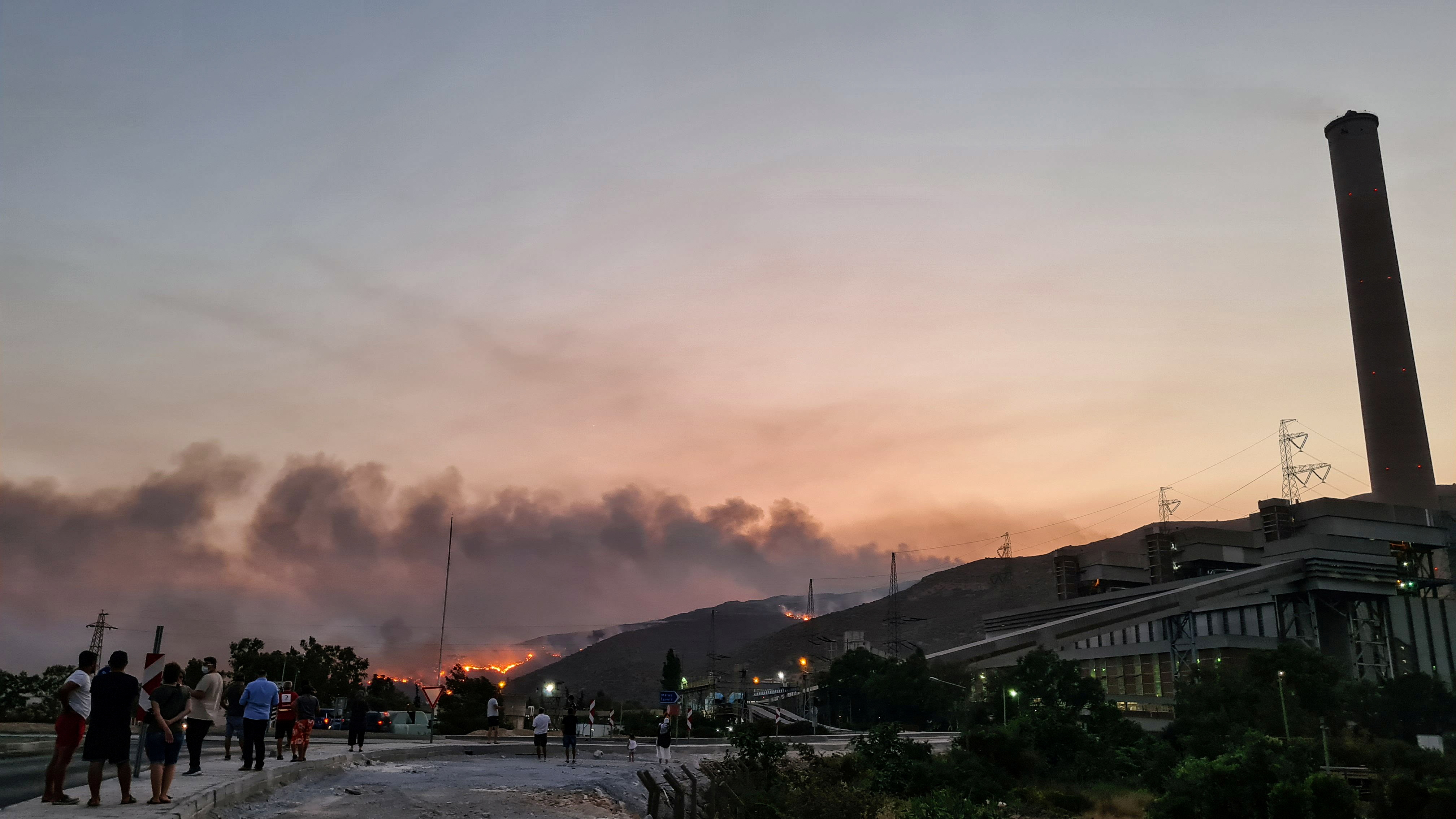 Flames and smoke fill the sky as residents watch the wildfire next to a thermal power station near Cokertme, a village in Bodrum region, Turkey, August 3, 2021. REUTERS/Kenan Gurbuz