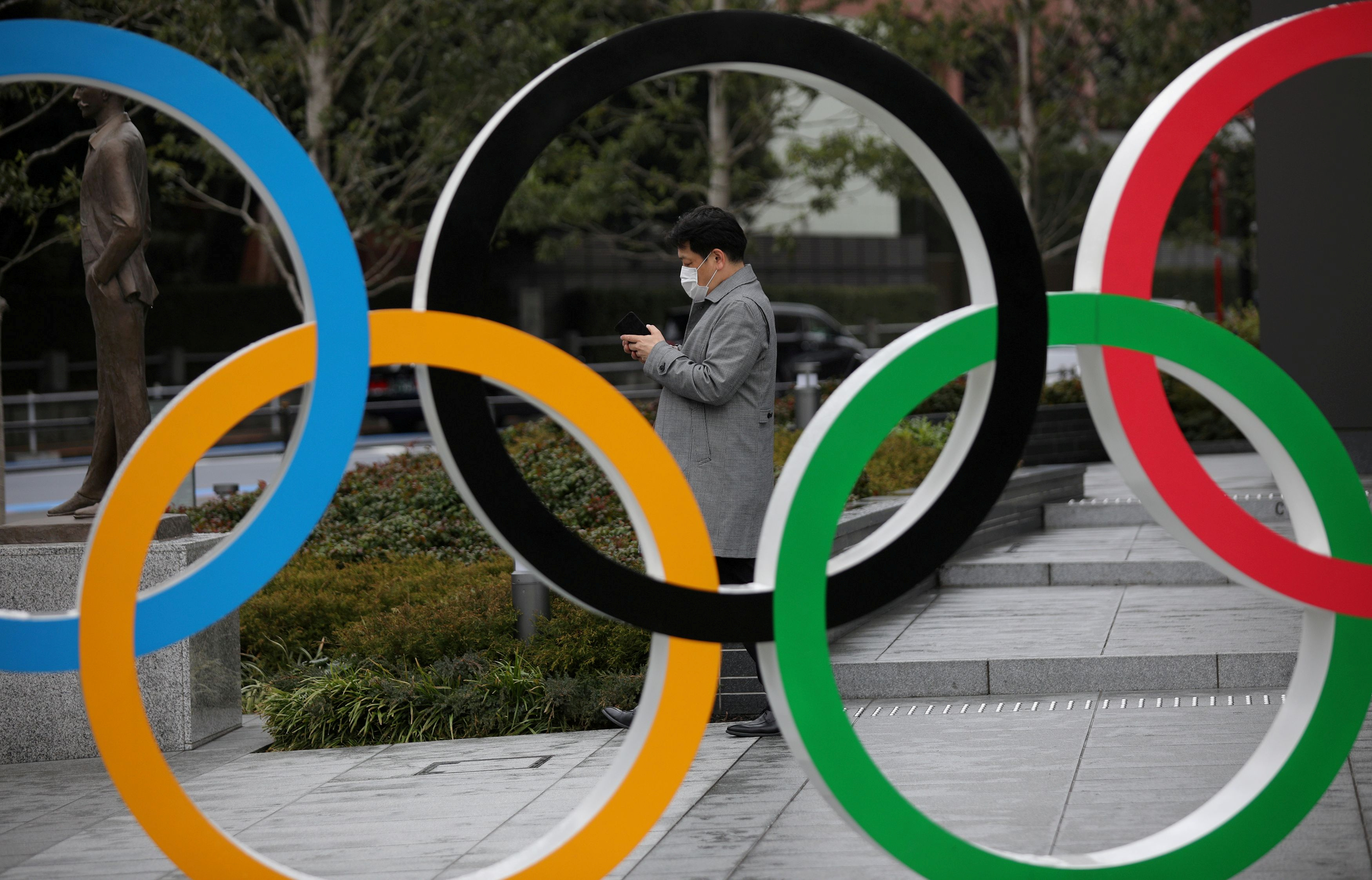 A man looks at his mobile phone next to The Olympic rings in front of the Japan Olympics Museum in Tokyo, Japan, March 4, 2020. REUTERS/Stoyan Nenov