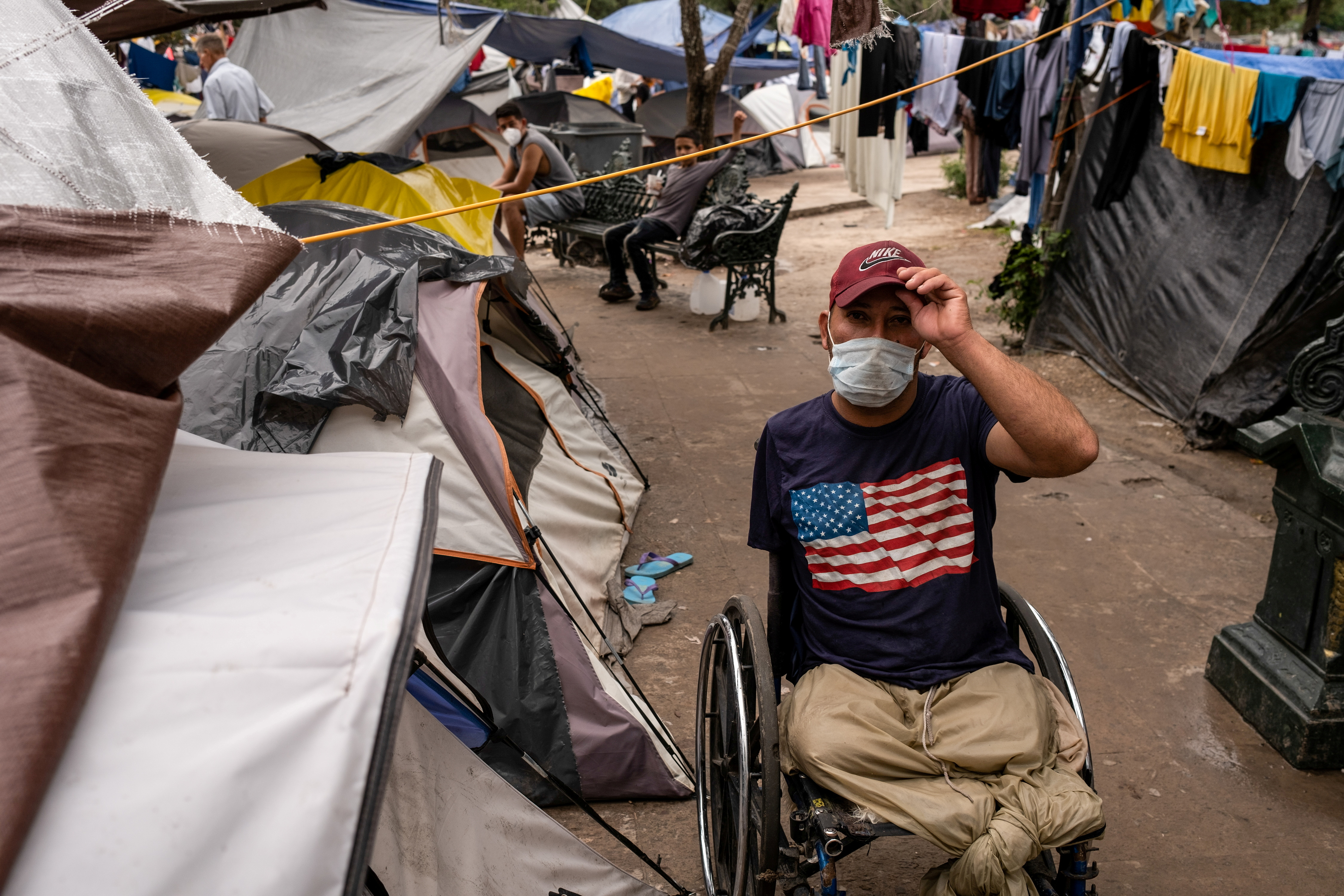 An asylum-seeking migrant from Honduras, Wilmer, 35, who was sent back to Mexico under Title 42 after crossing the border into the U.S. from Mexico, poses in his wheelchair in a public square where hundreds of migrants live in tents, in Reynosa, Mexico, July 10, 2021. REUTERS/Go Nakamura/File Photo