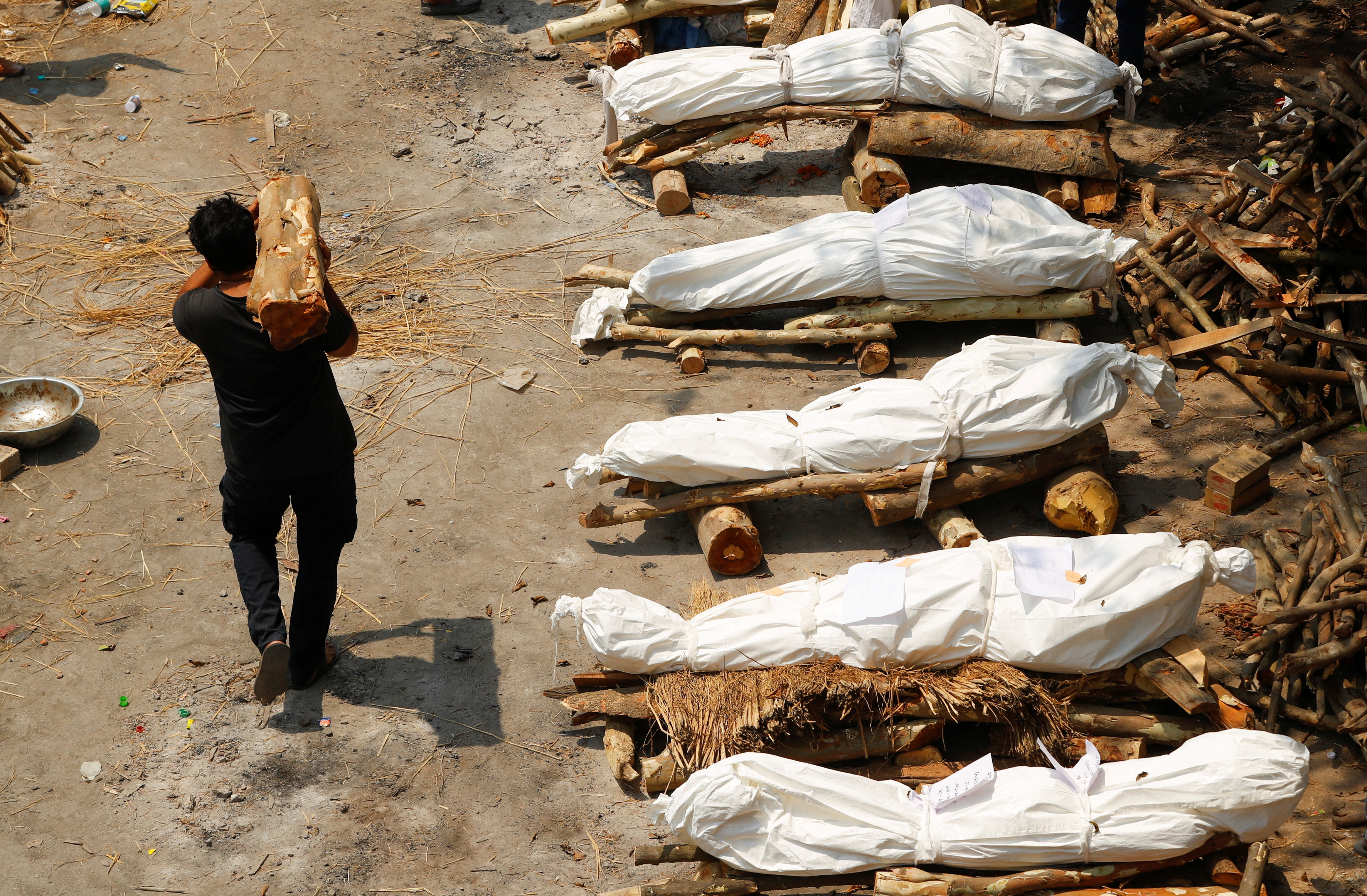 A man carrying wood walks past the funeral pyres of those who died from the coronavirus disease (COVID-19), during a mass cremation, at a crematorium in New Delhi, India April 26, 2021. REUTERS/Adnan Abidi