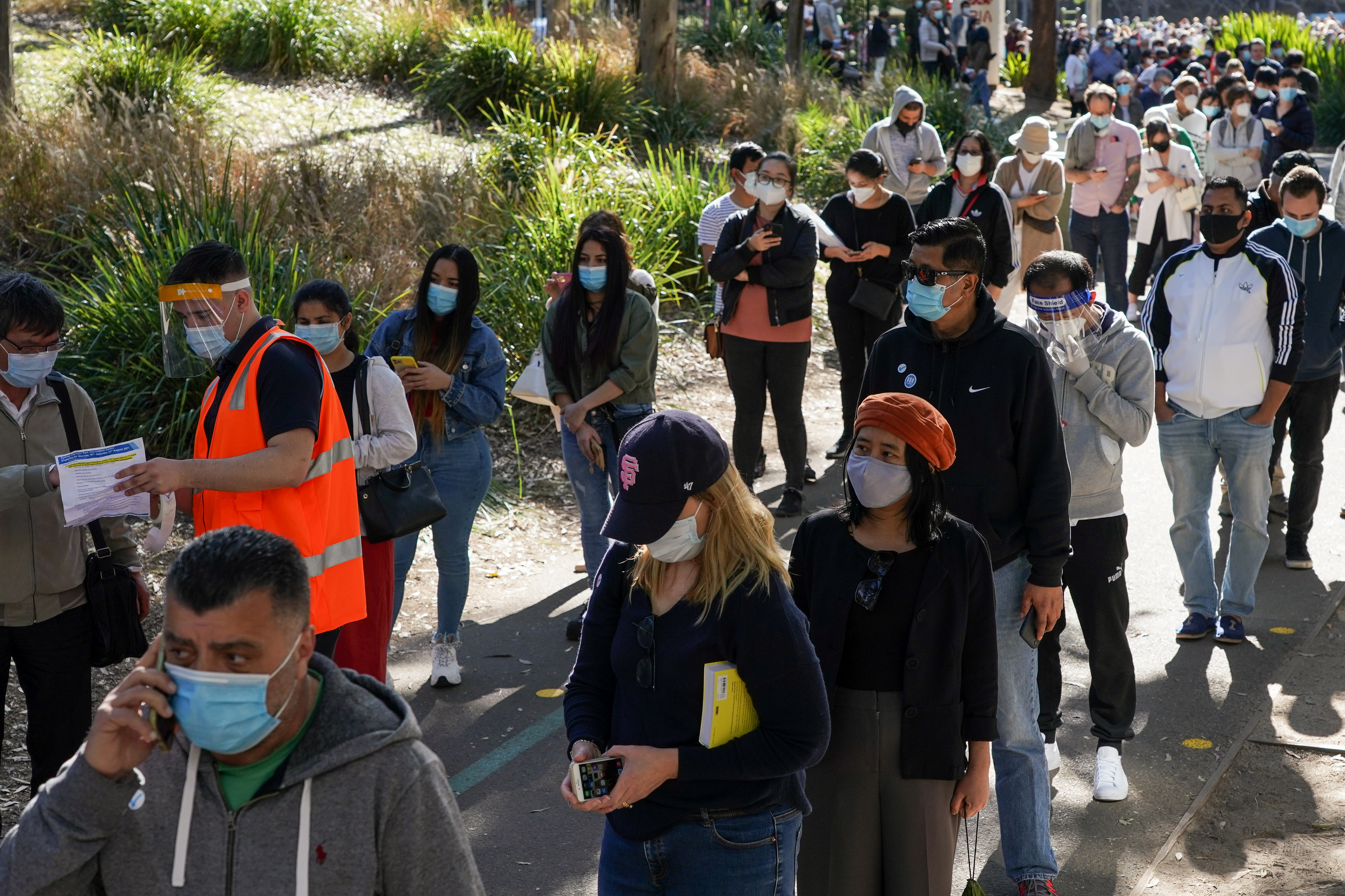 People wait in line outside a coronavirus disease (COVID-19) vaccination centre at Sydney Olympic Park during a lockdown to curb the spread of an outbreak in Sydney, Australia, August 16, 2021.  REUTERS/Loren Elliott