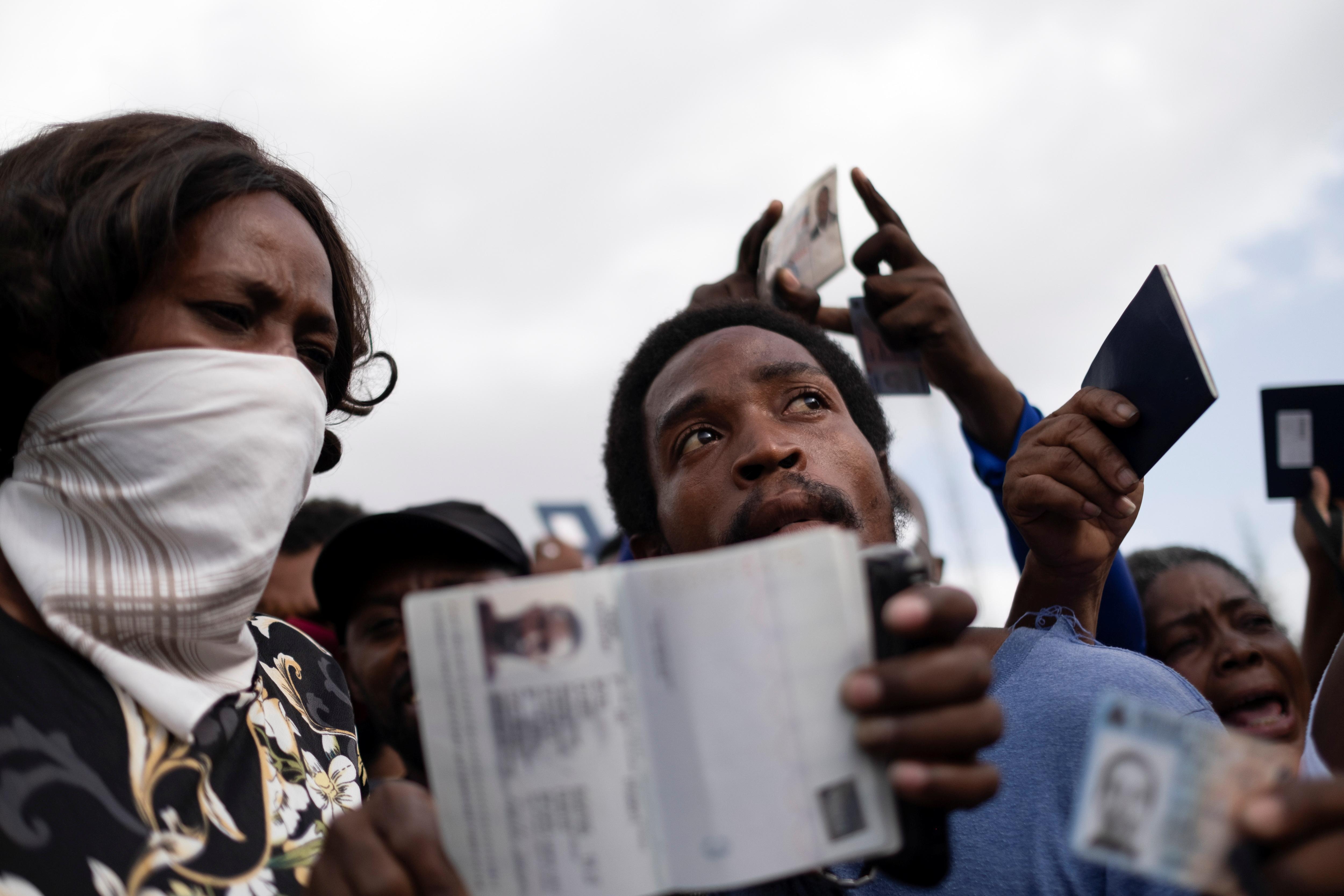 Los haitianos que solicitan asilo muestran sus pasaportes haitianos frente a la embajada de Estados Unidos, luego del asesinato del presidente Jovenel Moise, en Puerto Príncipe, Haití, el 9 de julio de 2021. REUTERS / Ricardo Arduengo