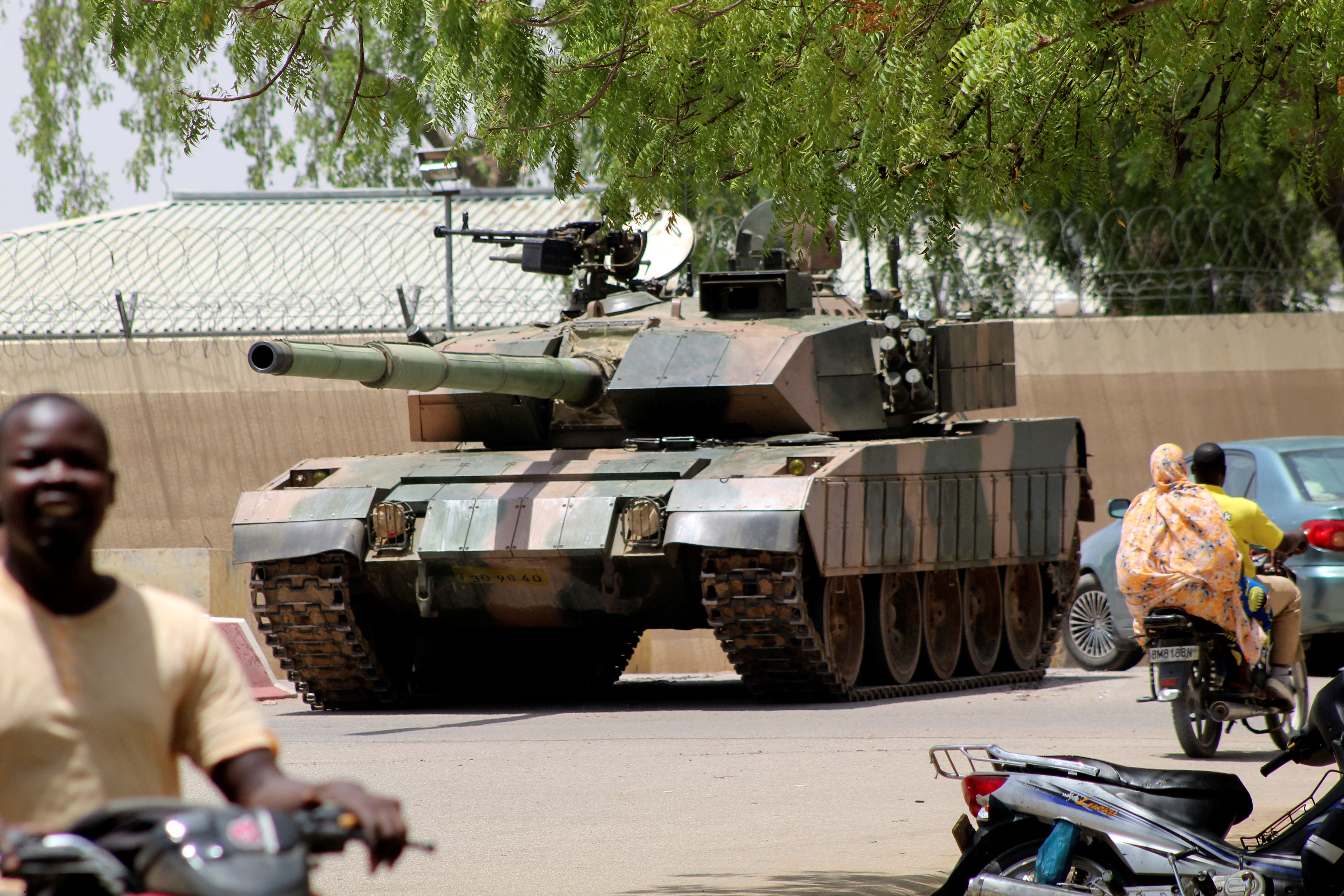 People drive past a Chad army tank near presidential palace, as fighters from the rebel Front for Change and Concord in Chad (FACT) appeared to be moving toward the capital according to the United States, in N'djamena, Chad April 19, 2021. REUTERS/ Stringer