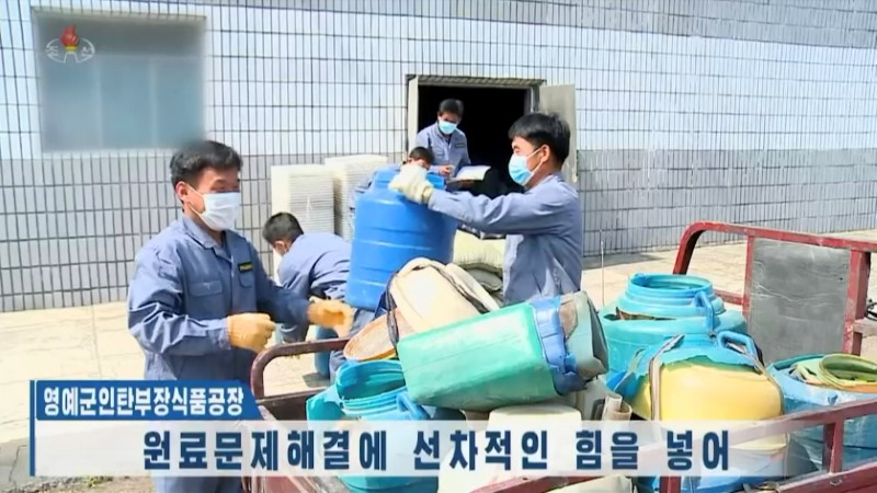 North Korean factory workers move plastic waste, in this still image taken from a video released by KRT, May 4, 2021. KRT/via REUTERS