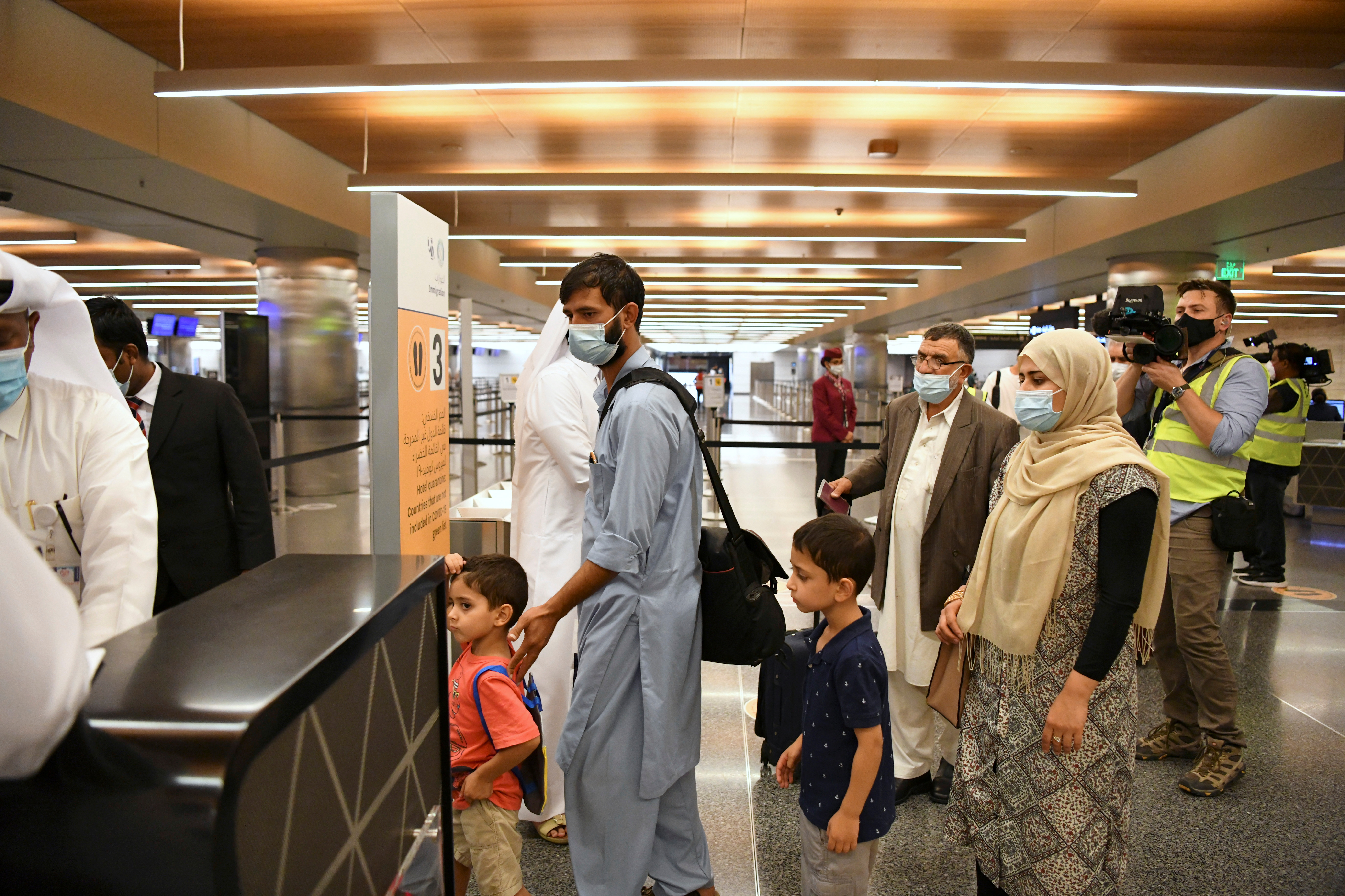 Passengers wait in line in the airport terminal upon arriving on a Qatar Airways plane from Kabul, Afghanistan, the first international commercial flight since the U.S. withdrawal from Afghanistan, in Doha, Qatar, September 9, 2021. REUTERS/Nooman Ben Amor