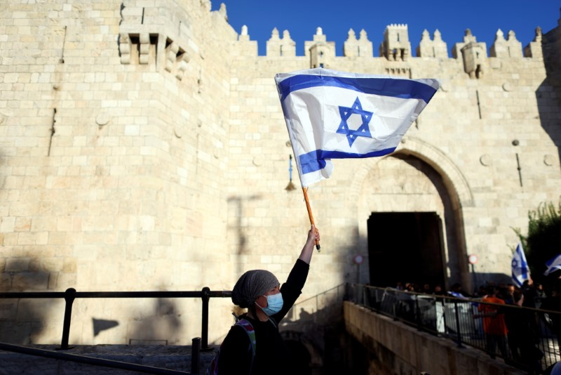 An Israeli woman holds a flag by Damascus gate just outside Jerusalem's Old City June 15, 2021. REUTERS/Ronen Zvulun