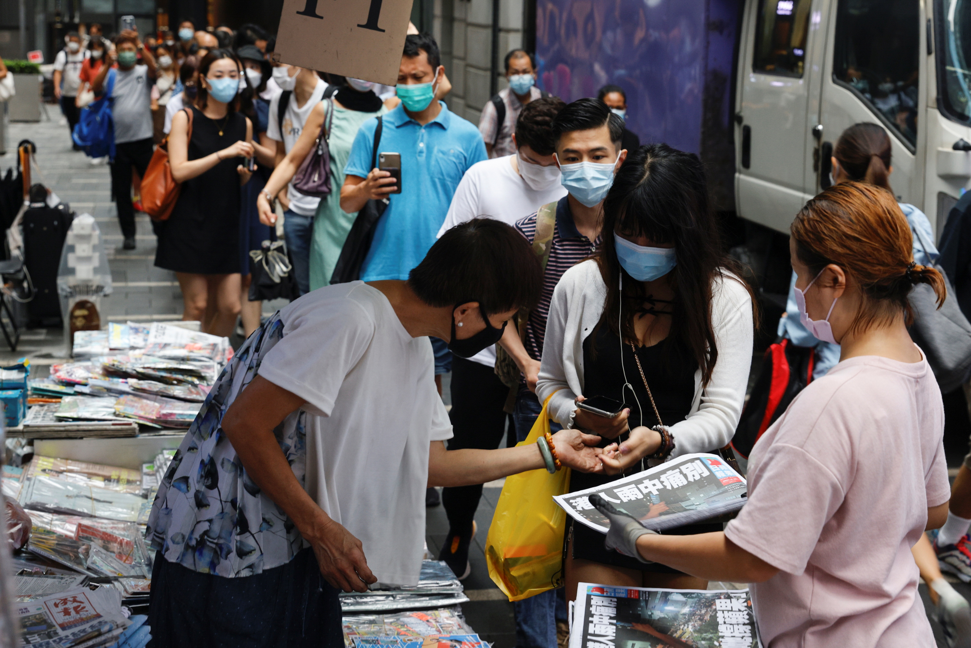 People queue to buy copies of the final edition of Apple Daily, published by Next Digital, in the Central financial district, in Hong Kong, China June 24, 2021. REUTERS/Tyrone Siu