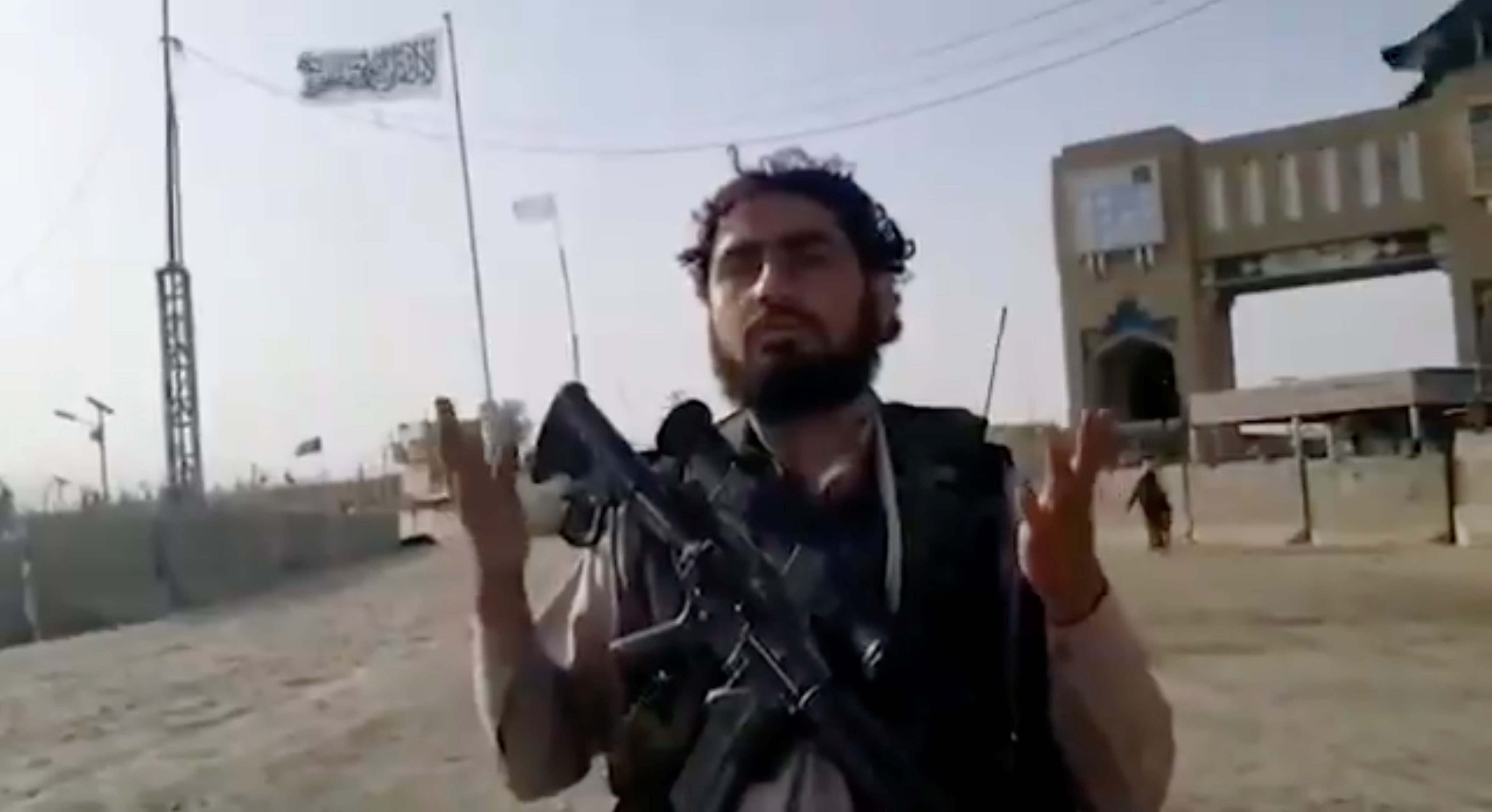 A man holding a gun speaks as an Islamic Emirate of Afghanistan flag flutters in front of the friendship gate of Afghanistan and Pakistan at the Wesh-Chaman border crossing, Spin Boldak, Afghanistan July 14, 2021, in this screen grab obtained from a video. TALIBAN HANDOUT via REUTERS