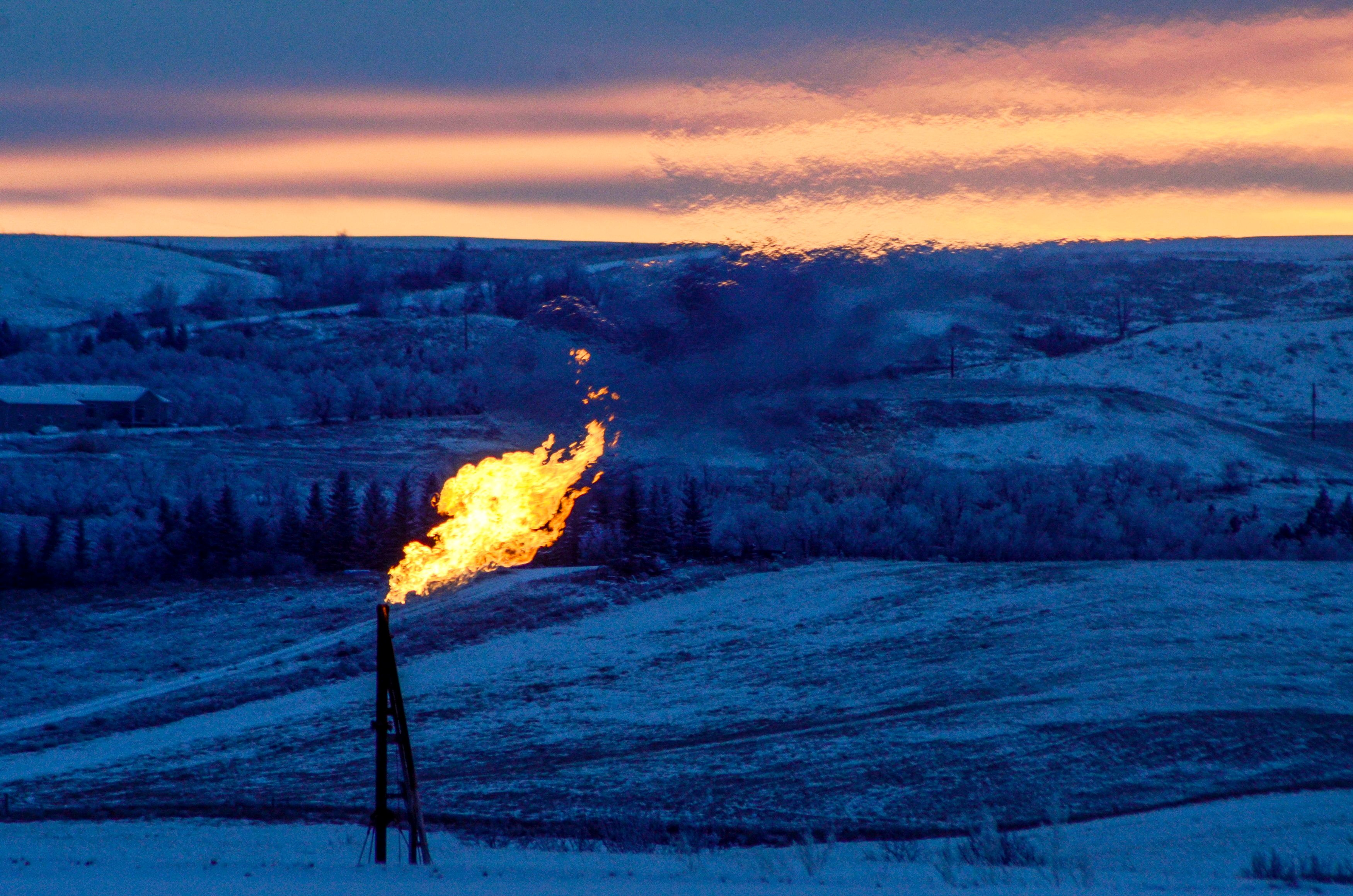 FILE PHOTO: A natural gas flare on an oil well pad burns as the sun sets outside Watford City, North Dakota January 21, 2016. REUTERS/Andrew Cullen/File Photo/File Photo