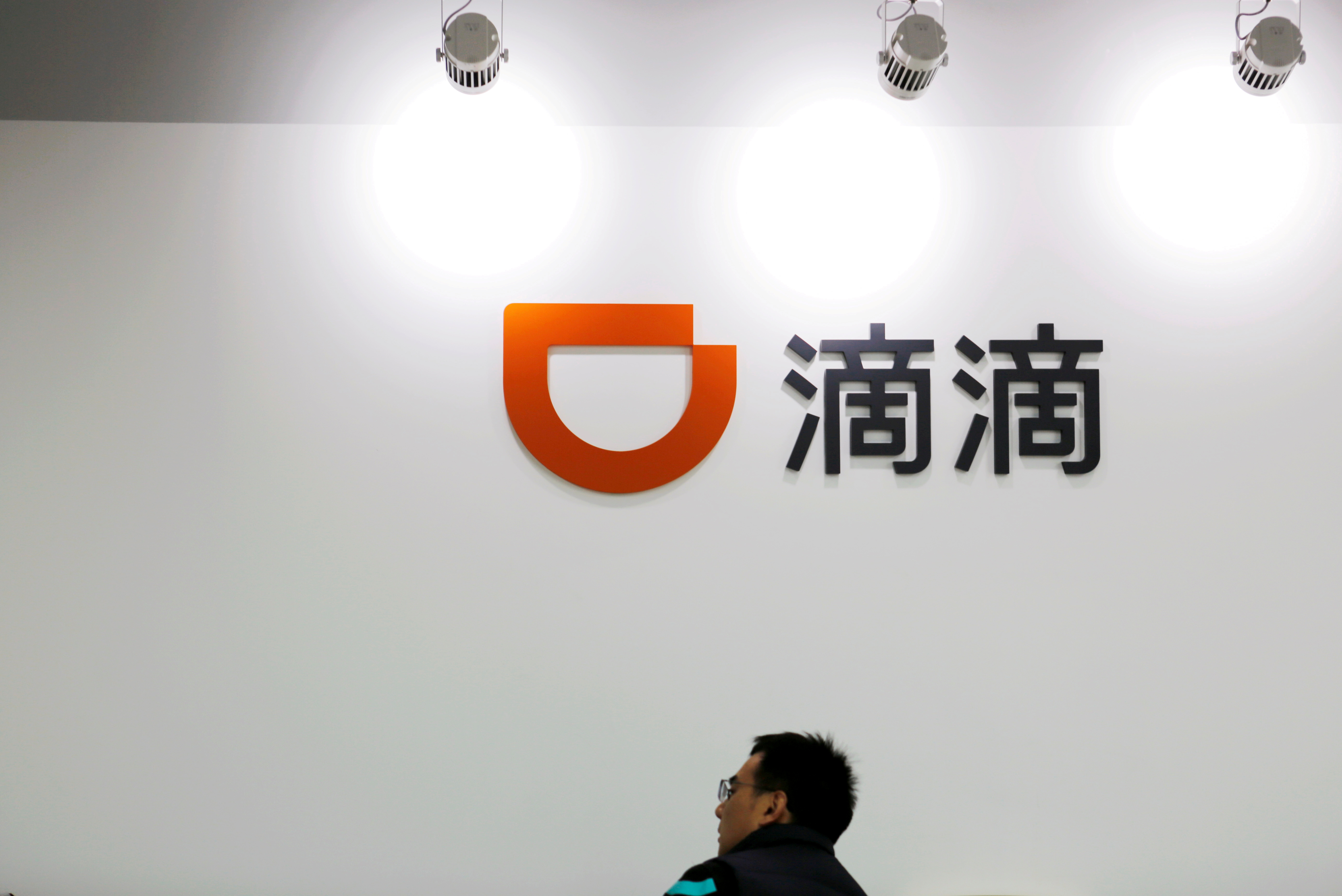 A man is seen under a Didi logo at the headquarters of Didi Chuxing in Beijing, China November 20, 2020. REUTERS/Florence Lo