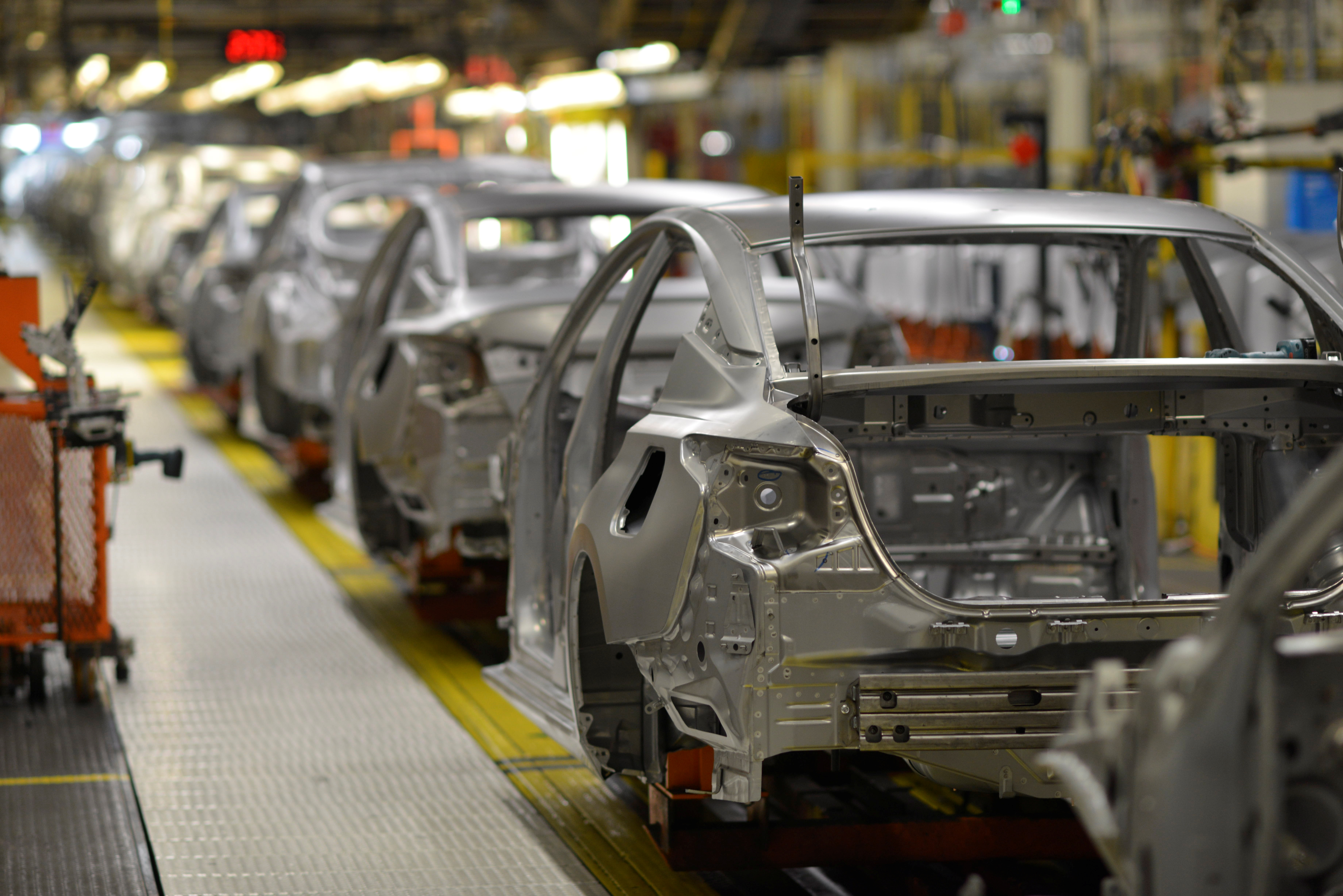 Frames of various car models make their way down the flex line at Nissan Motor Co