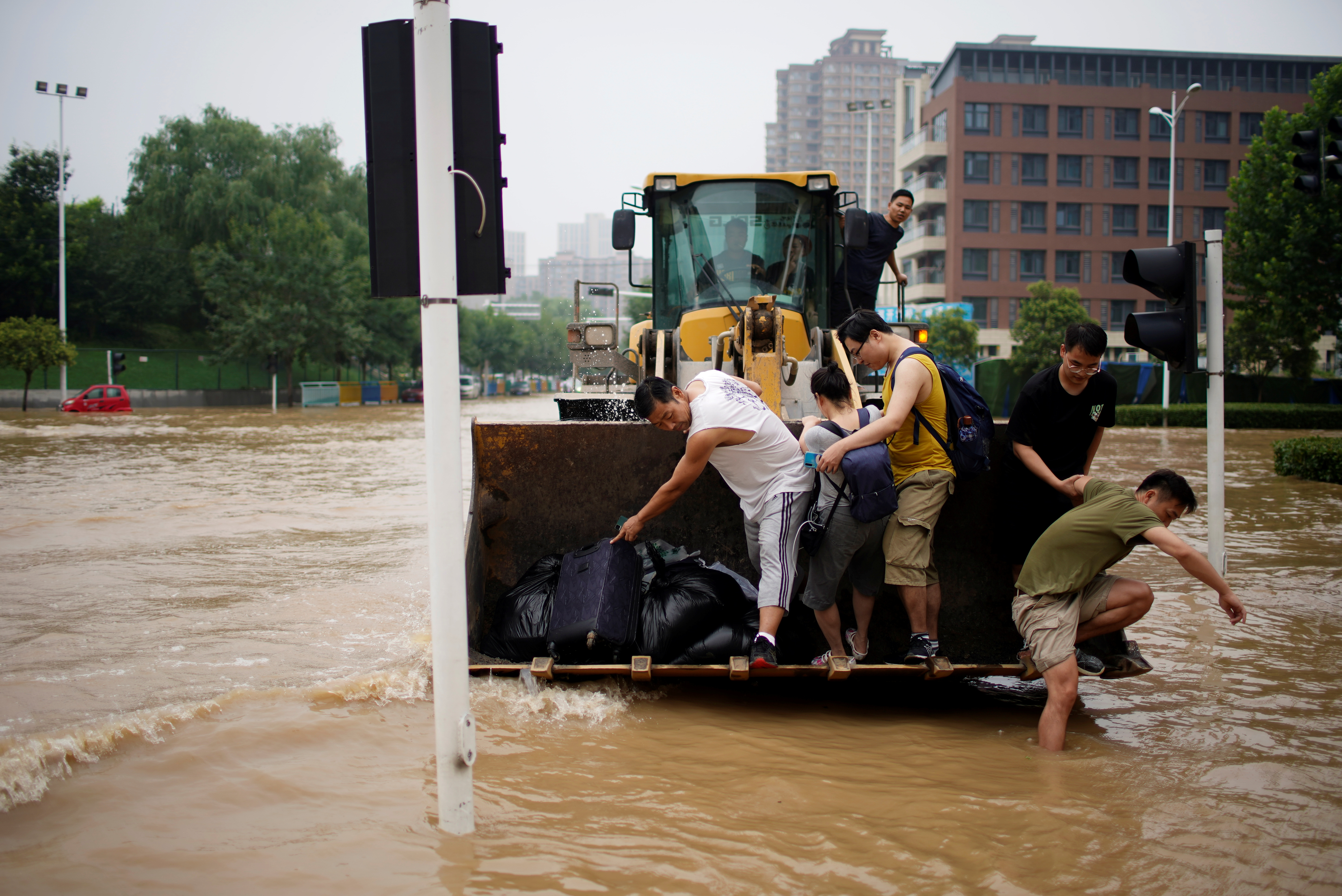 People ride on a front loader as they make their way through a flooded road following heavy rainfall in Zhengzhou, Henan province, China July 23, 2021. REUTERS/Aly Song