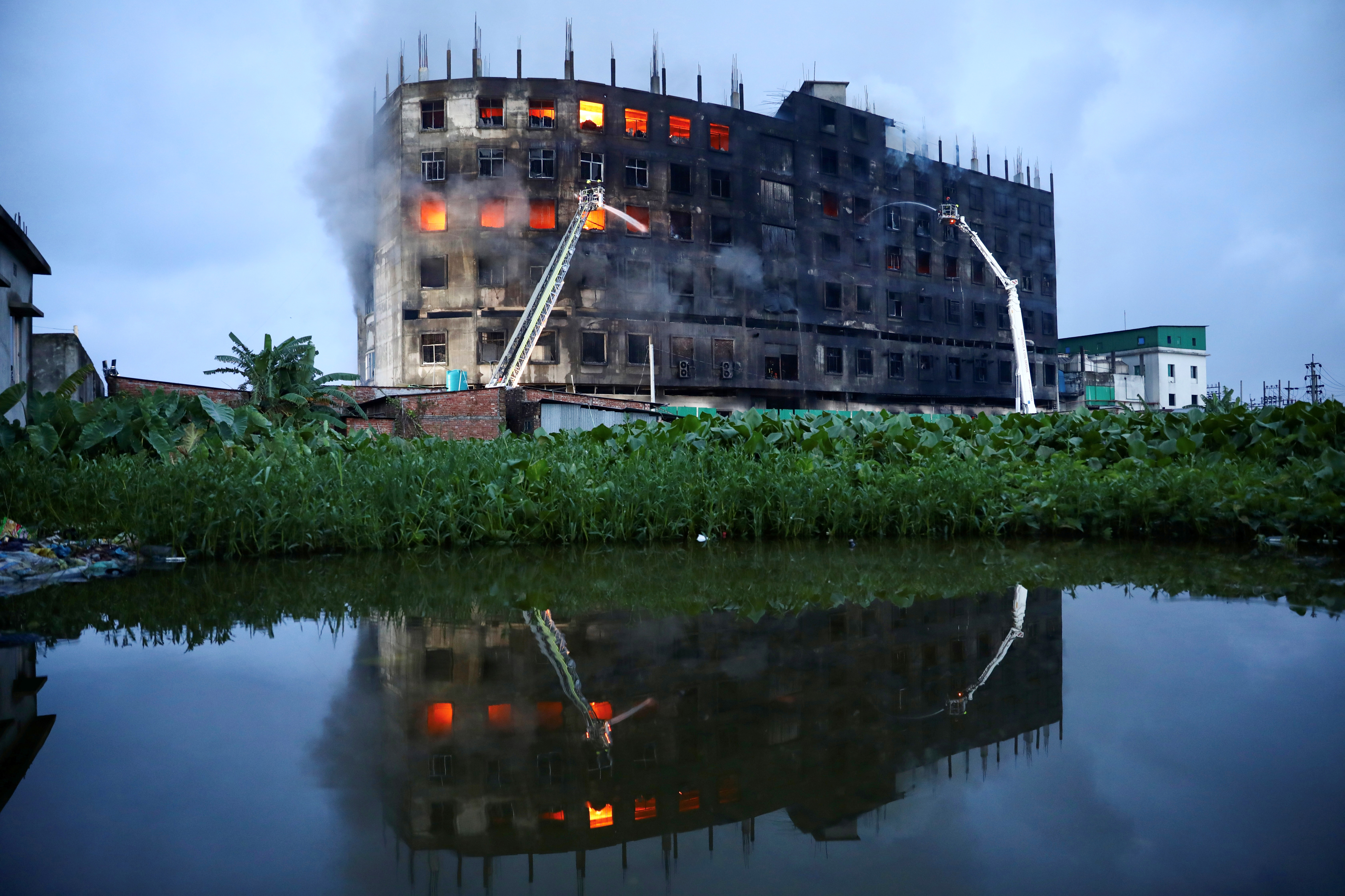 Flames rise the morning after a fire broke out at a factory named Hashem Foods Ltd. in Rupganj of Narayanganj district, on the outskirts of Dhaka, Bangladesh, July 9, 2021. REUTERS/Mohammad Ponir Hossain