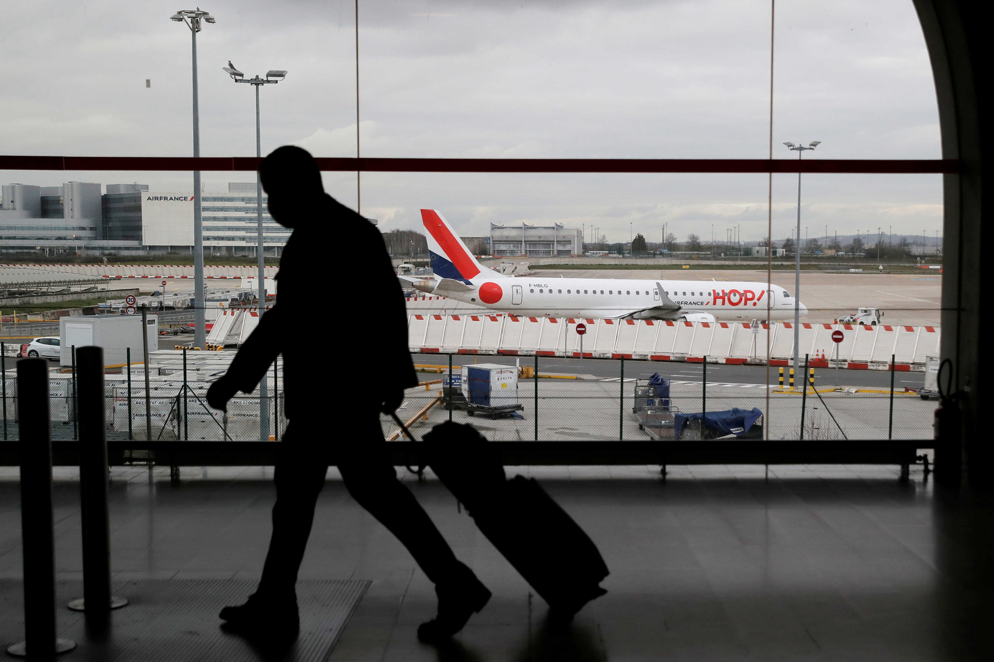A man walks inside a Terminal at Paris Charles de Gaulle airport in Roissy near Paris as France closed its borders to travellers outside European Union due to restrictions against the spread of the coronavirus disease (COVID-19) in France, February 5, 2021. REUTERS/Gonzalo Fuentes/File Photo