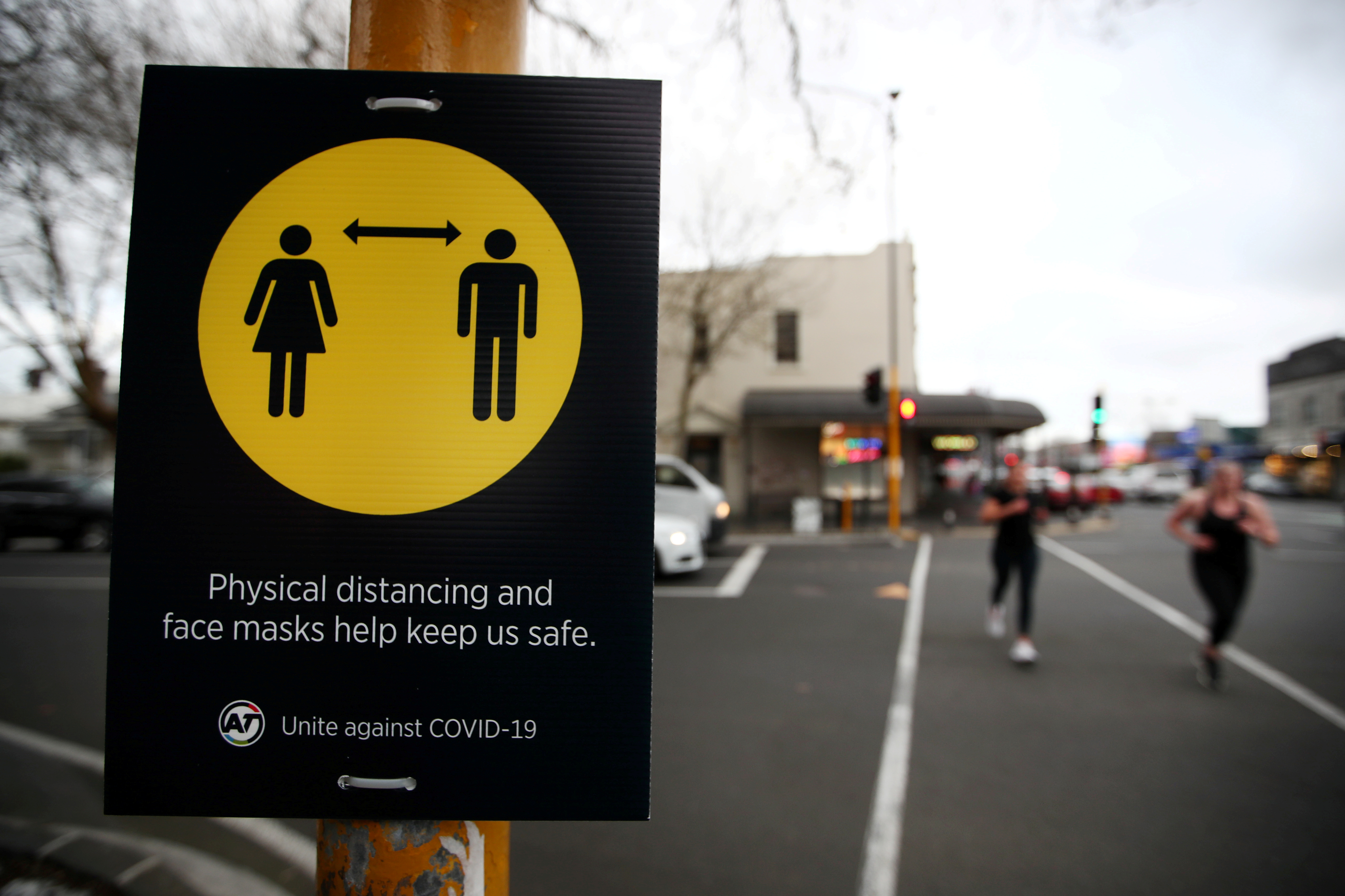 People jog past a social distancing sign on the first day of New Zealand