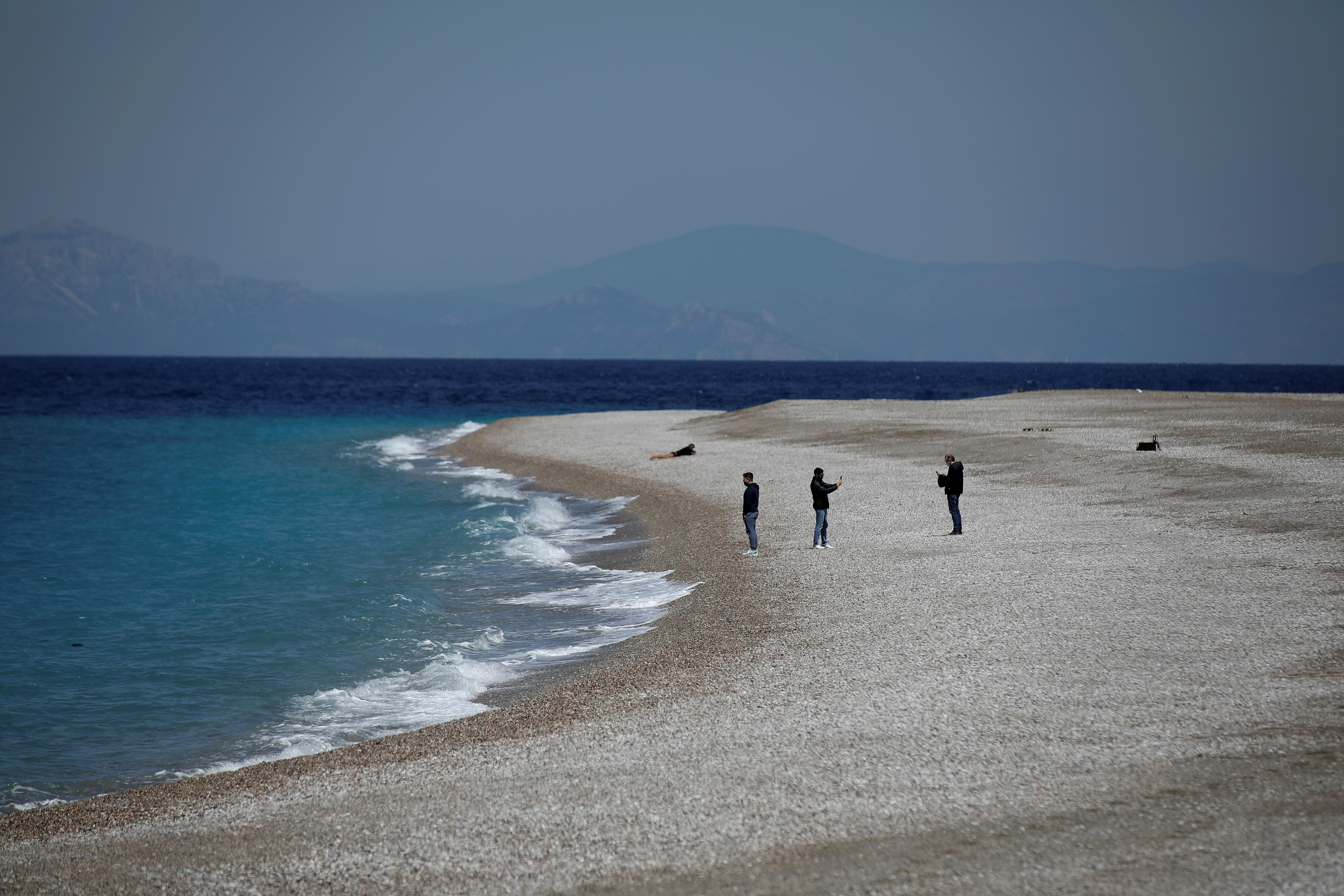 People stand on Elli Beach, amid the coronavirus disease (COVID-19) pandemic, on the island of Rhodes, Greece, April 12, 2021. REUTERS/Louiza Vradi