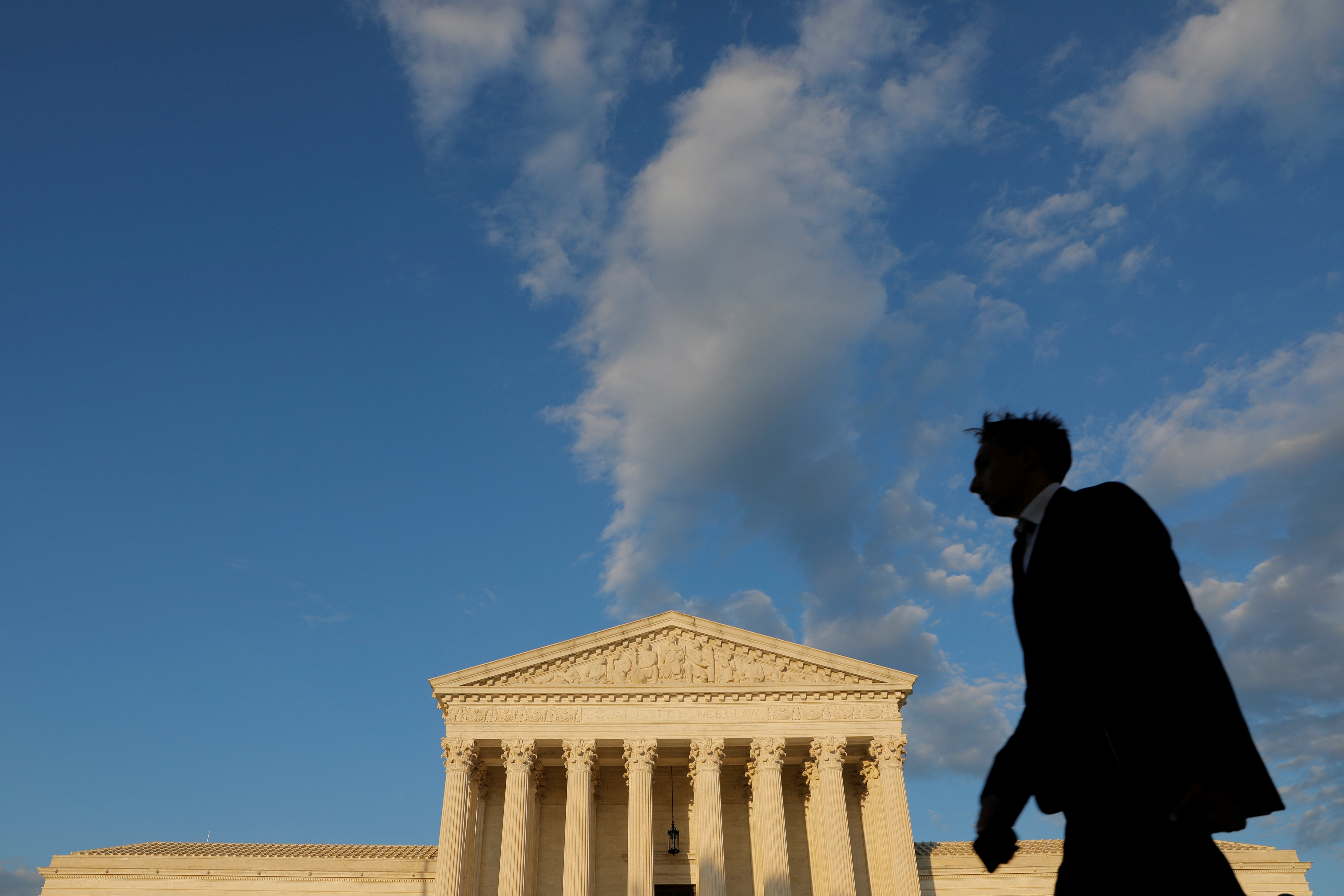 A person walks past the United States Supreme Court Building in Washington, D.C., U.S., May 13, 2021. REUTERS/Andrew Kelly/File Photo