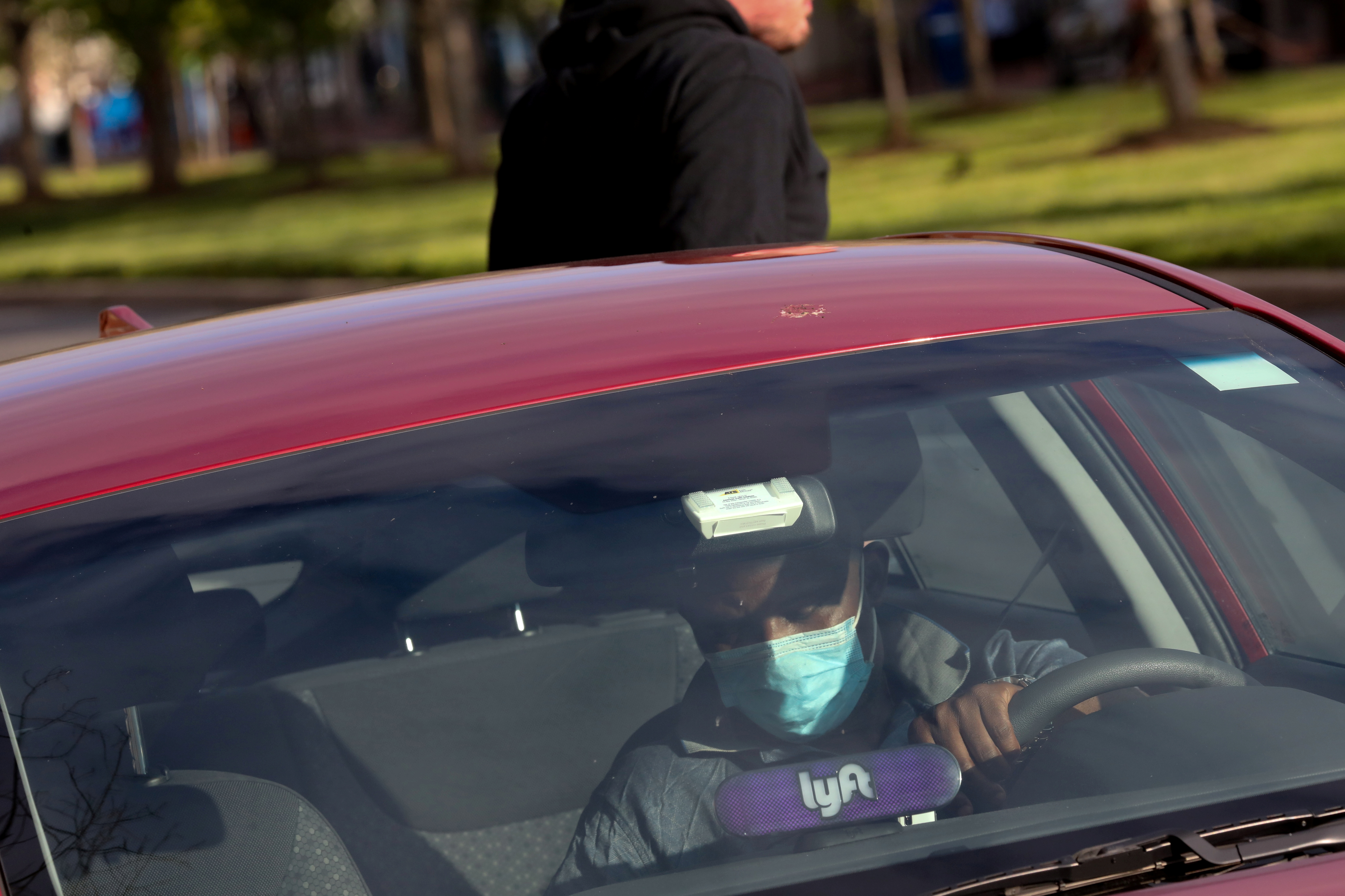 A Lyft rideshare driver wears a mask during the coronavirus outbreak, as he leaves passengers in the U.S. Capitol Hill neighborhood in Washington, U.S. April 1, 2020.  REUTERS/Jonathan Ernst/File Photo