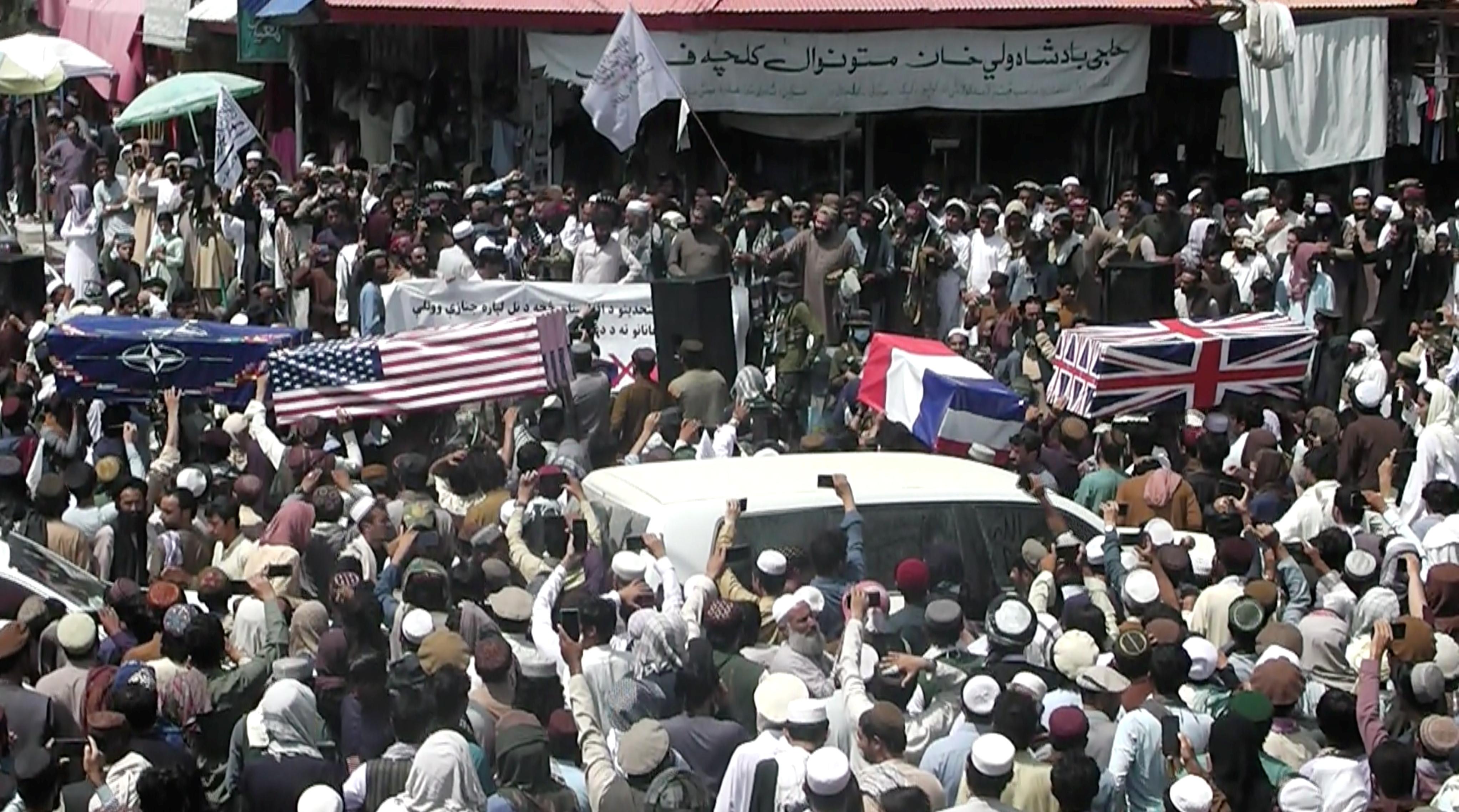 Crowd carries makeshift coffins draped in NATO's, U.S. and a Union Jack flags during a pretend funeral  on a street in Khost, Afghanistan August 31, 2021, in this screen grab obtained from a social media video. ZHMAN TV/via REUTERS