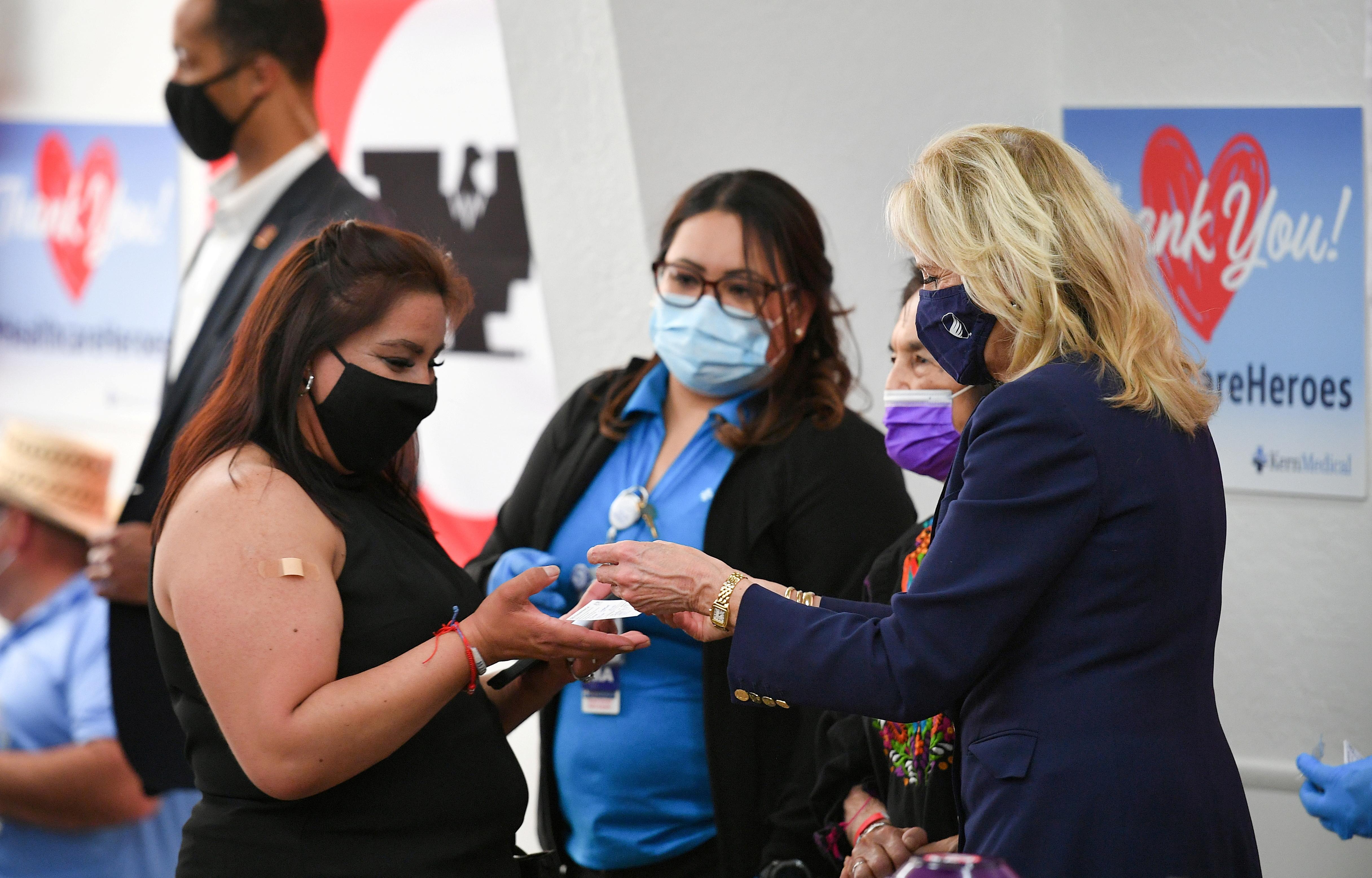 Đệ nhất phu nhân Hoa Kỳ Jill Biden trao thẻ tiêm chủng cùng với ghim cho một phụ nữ vừa được tiêm mũi vắc xin thứ hai ở Delano, California vào ngày 31 tháng 3 năm 2021. Mandel Ngan / Pool via REUTERS / File Photo