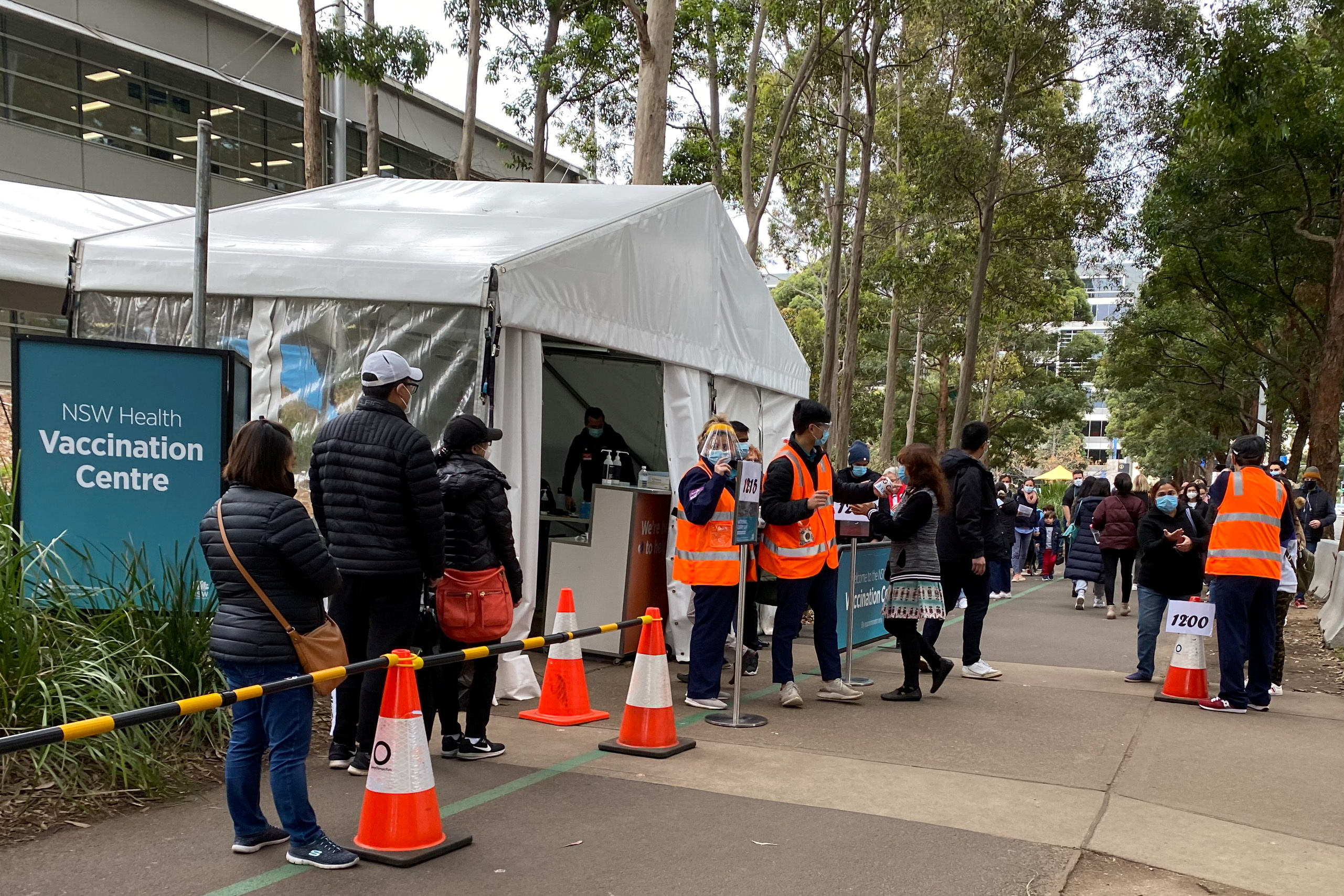 People wait in line outside a coronavirus disease (COVID-19) vaccination centre at Sydney Olympic Park in Sydney, Australia, July 14, 2021. REUTERS/Jane Wardell