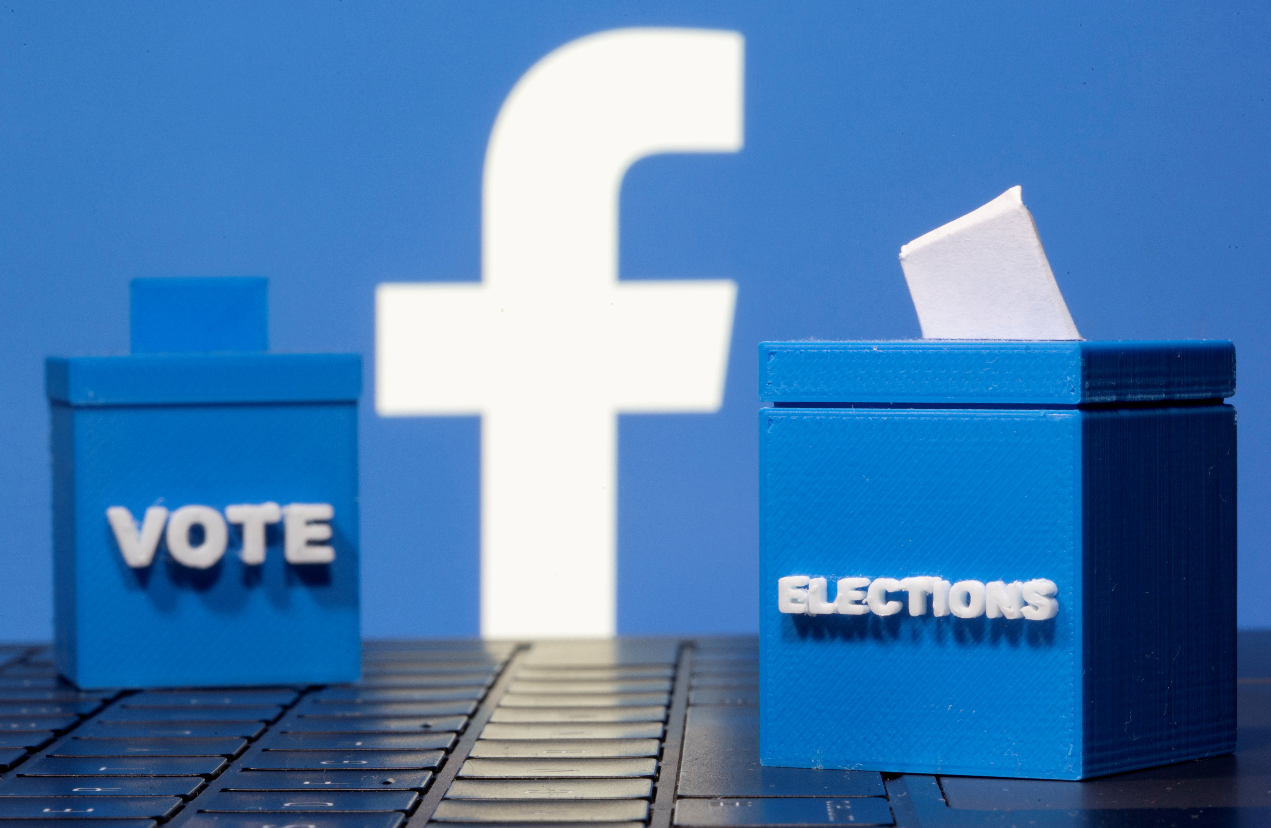 3D-printed ballot boxes are seen in front of a displayed Facebook logo in this illustration taken November 4, 2020. REUTERS/Dado Ruvic/Illustration/File Photo