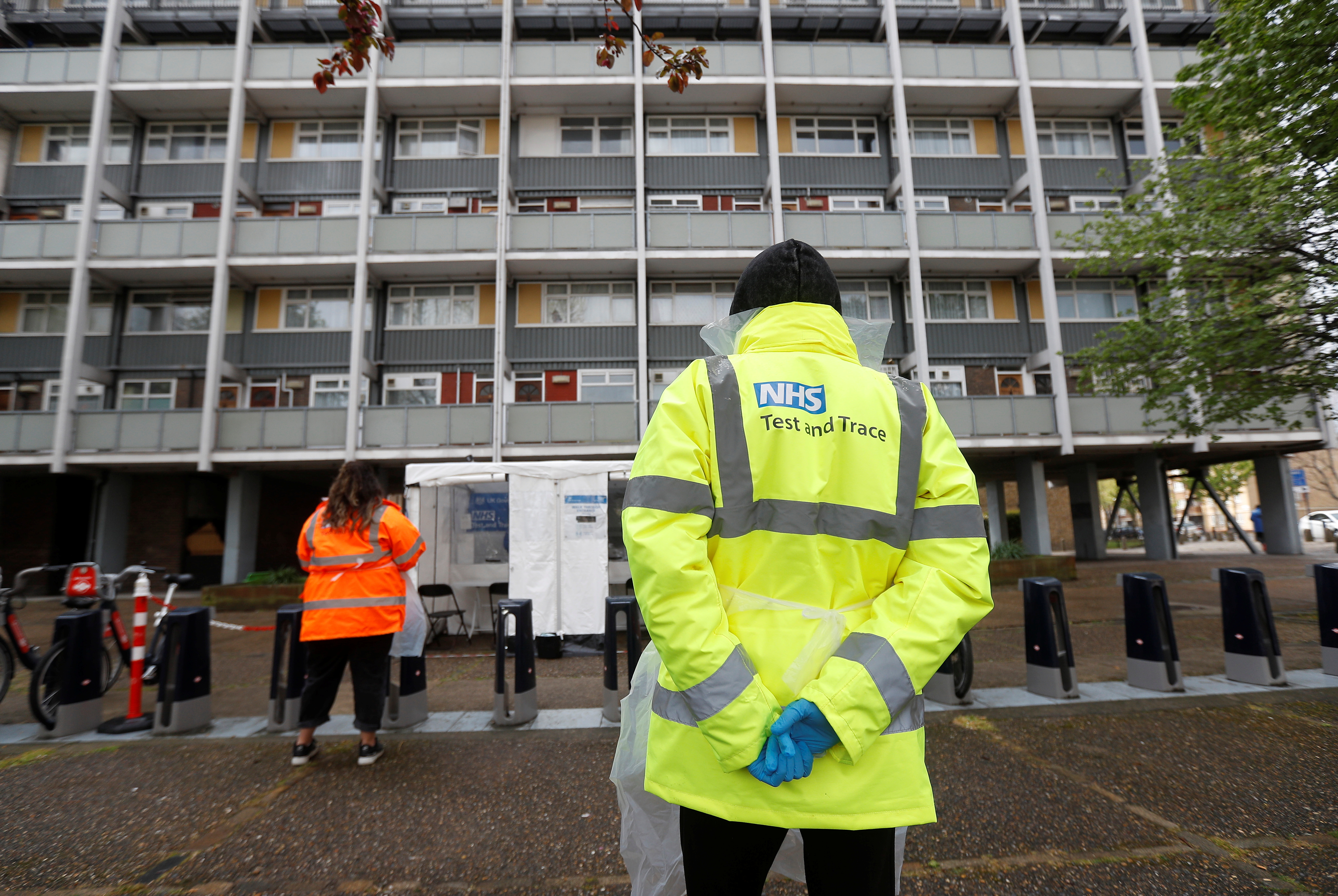 NHS workers stand near a coronavirus disease (COVID-19) mobile testing unit in Tower Hamlets, London, Britain, May 2, 2021. REUTERS/Peter Nicholls