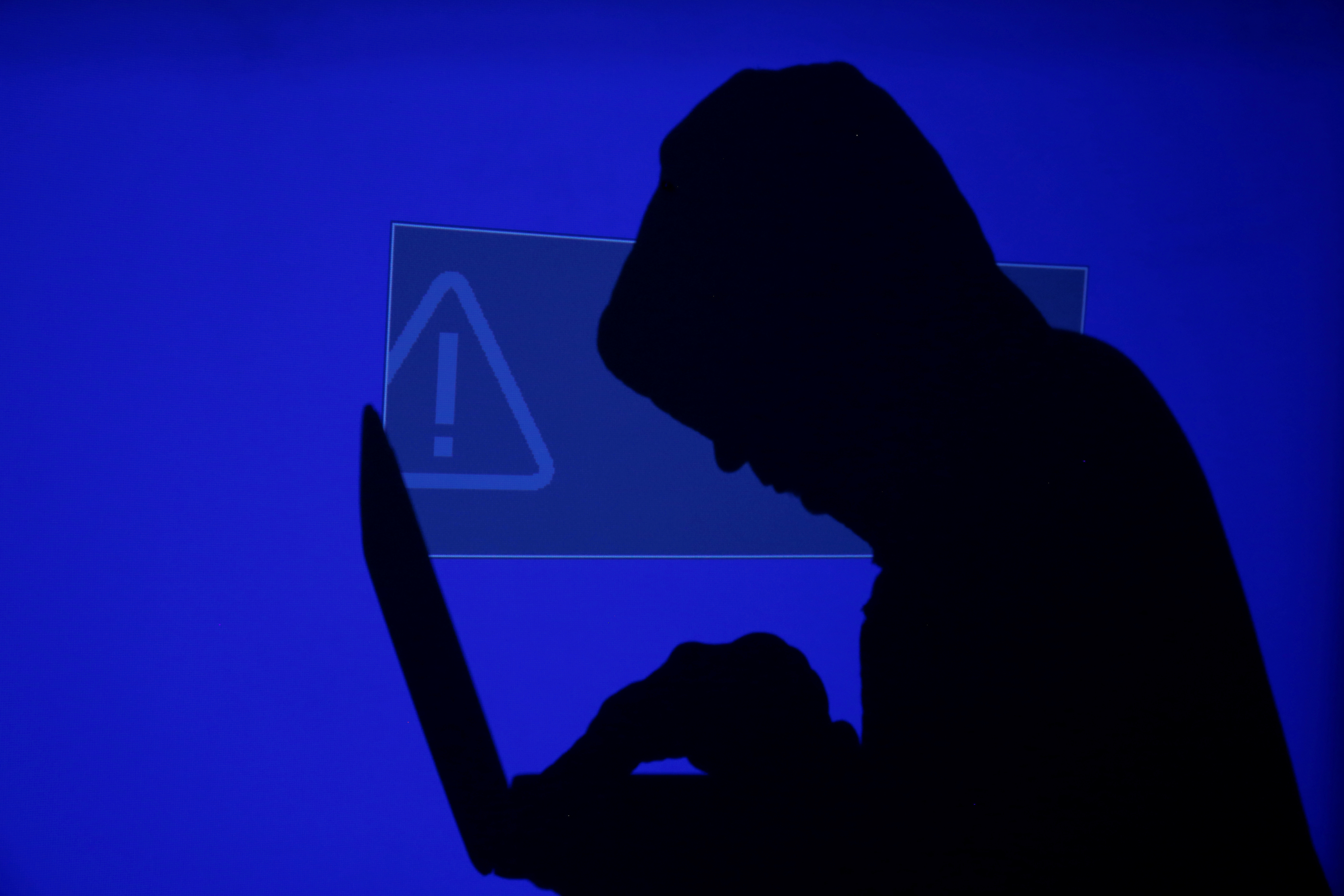 A hooded man holds a laptop computer as blue screen with an exclamation mark is projected on him in this illustration picture taken on May 13, 2017. REUTERS/Kacper Pempel/Illustration/File Photo