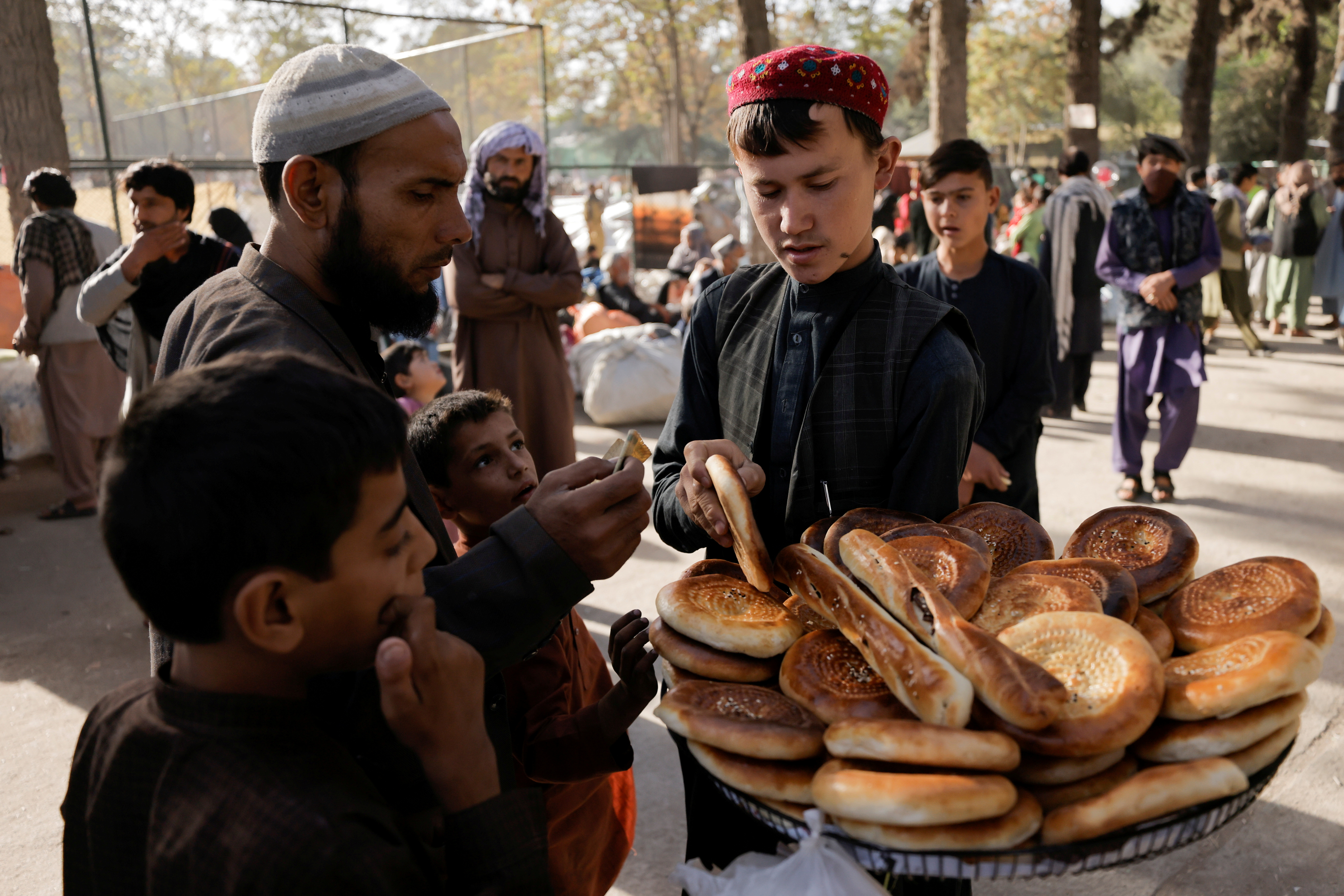 A boy sells bread at a makeshift shelter for displaced Afghan families, who are fleeing the violence in their provinces, at Shahr-e Naw park, in Kabul, Afghanistan October 4, 2021. REUTERS/Jorge Silva/Files