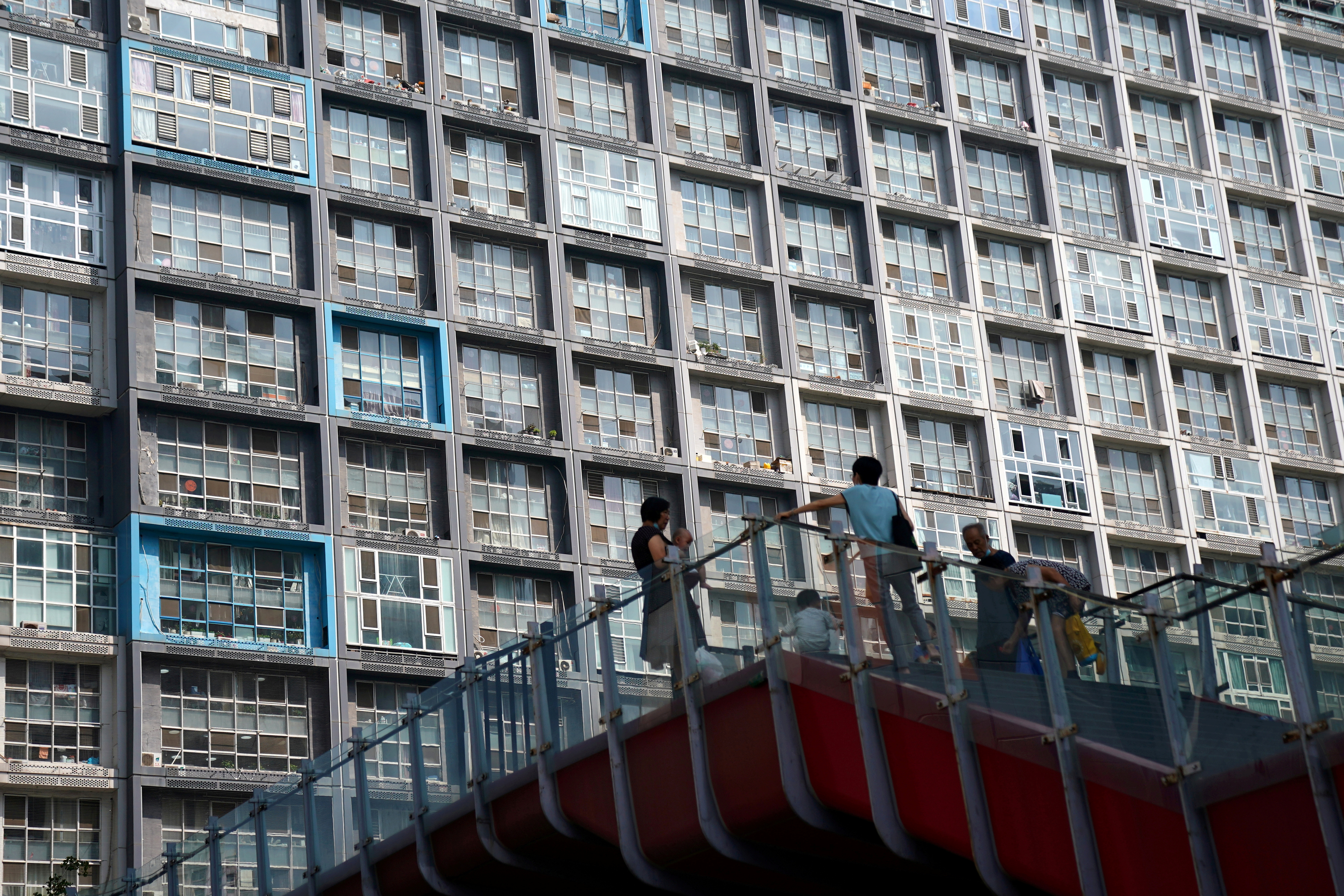 People wearing face masks are seen on an overpass in front of a residential building in Beijing, China August 11, 2020. Picture taken August 11, 2020. REUTERS/Tingshu Wang
