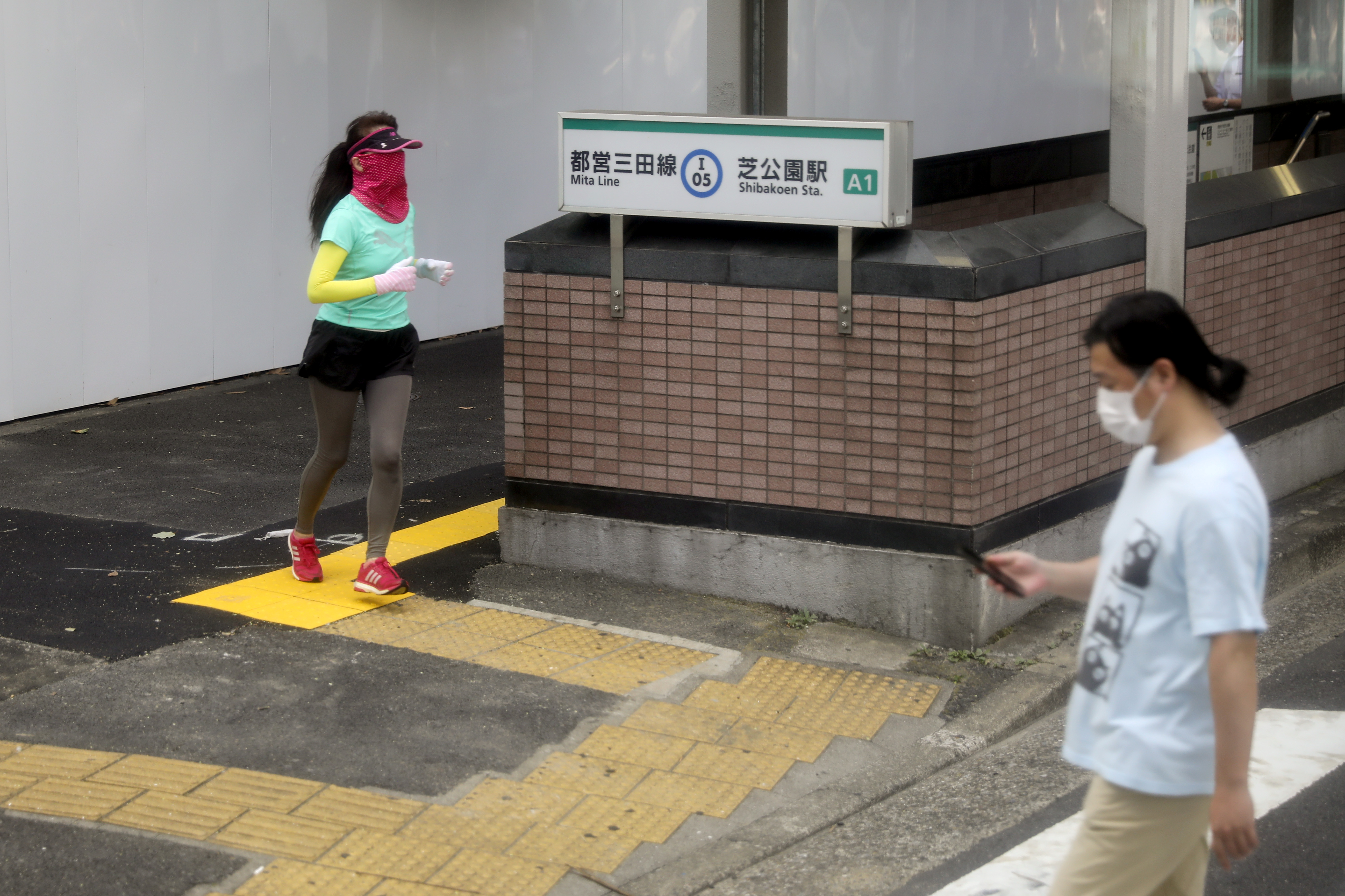 People wearing face masks pass Shibakoen Station during the coronavirus disease (COVID-19) pandemic in Tokyo, Japan, July 25, 2021.     REUTERS/Kevin Coombs