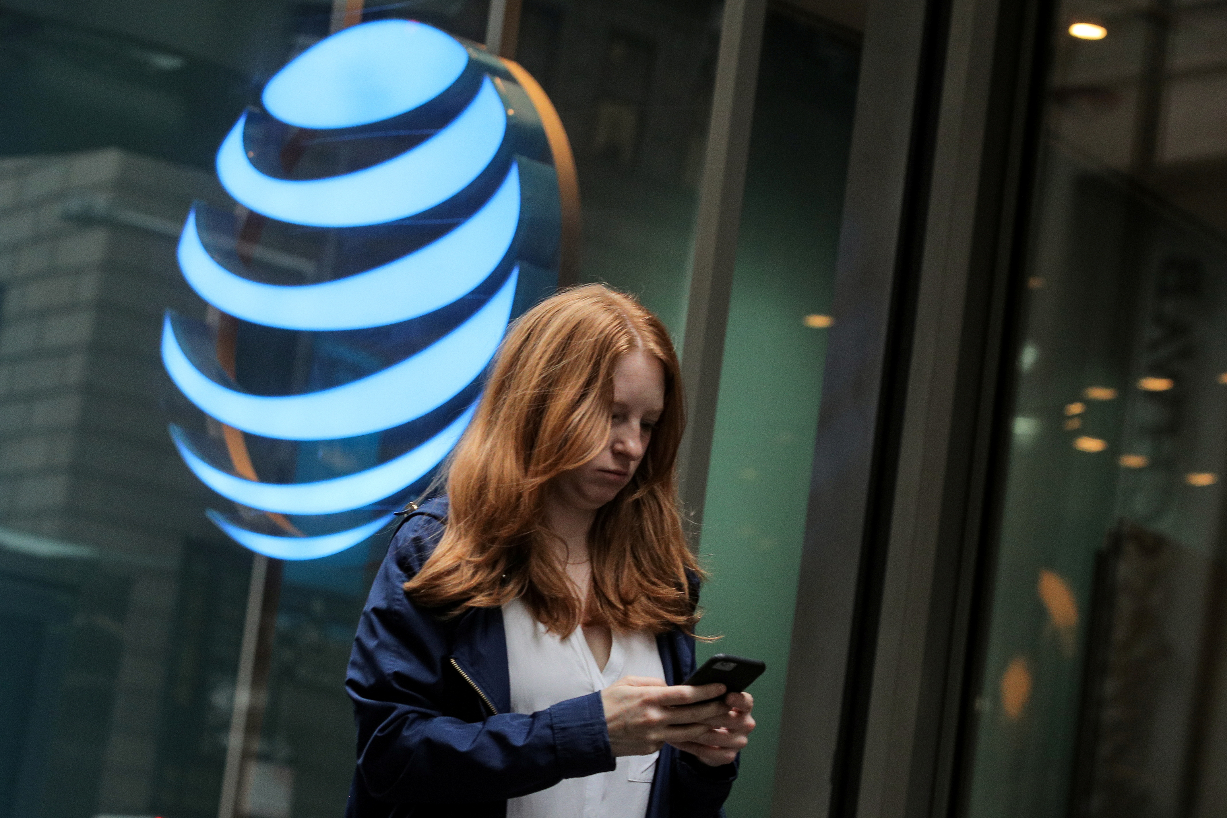 A woman uses her phone as she passes by an AT&T store on Wall St. in New York, U.S., June 19, 2019. REUTERS/Brendan McDermid/File Photo