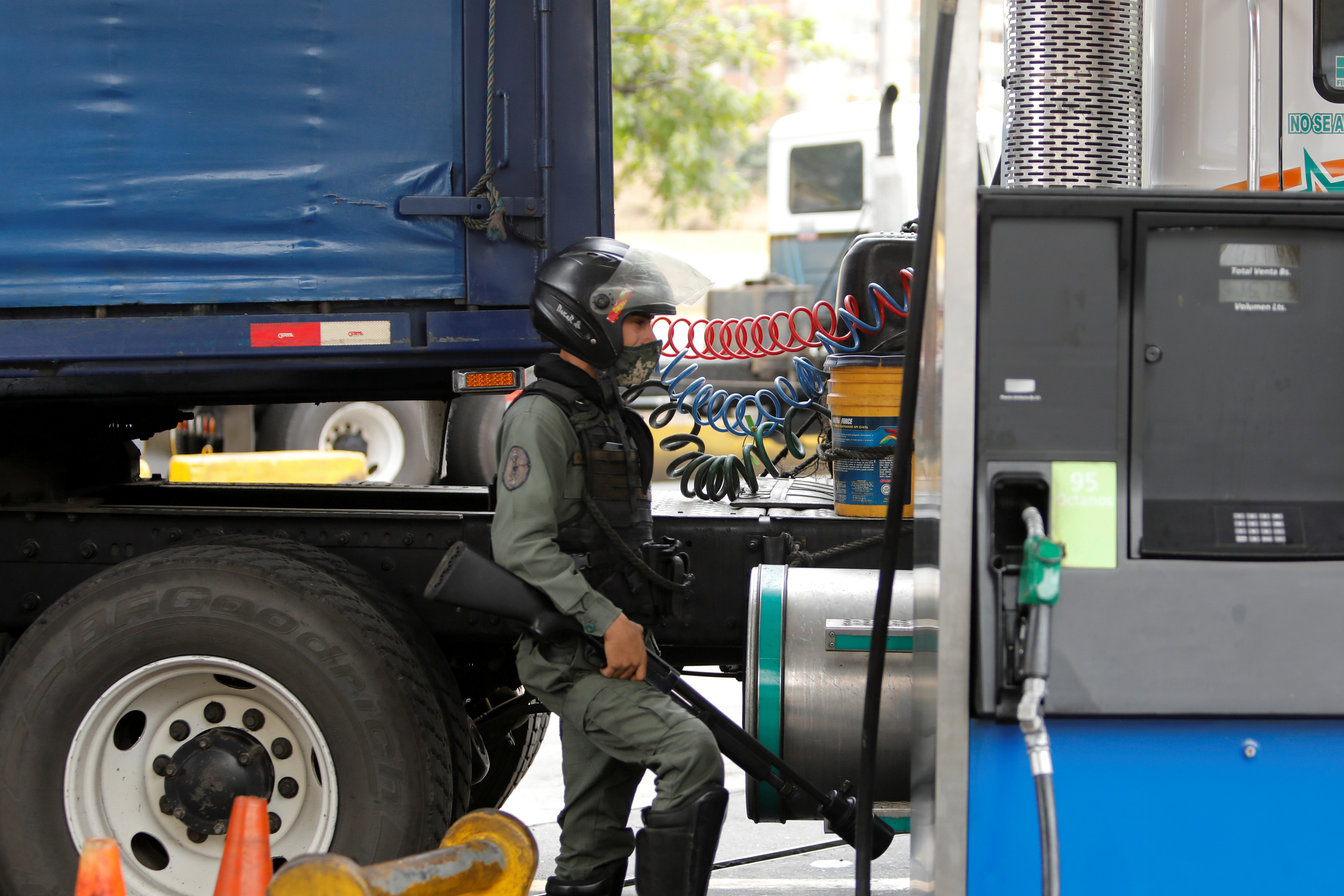 A member of the Bolivarian National Guard keeps watch at a gas station as trailer trucks line up along an avenue to fill up their tanks as part of a growing diesel shortage, in Caracas, Venezuela March 5, 2021. REUTERS/Leonardo Fernandez Viloria