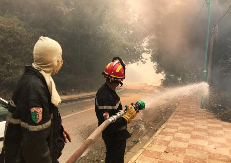 A firefighter uses a water hose during a forest fire in Ain al-Hammam village in the Tizi Ouzou region, east of Algiers, Algeria August 10, 2021. REUTERS/Abdelaziz Boumzar