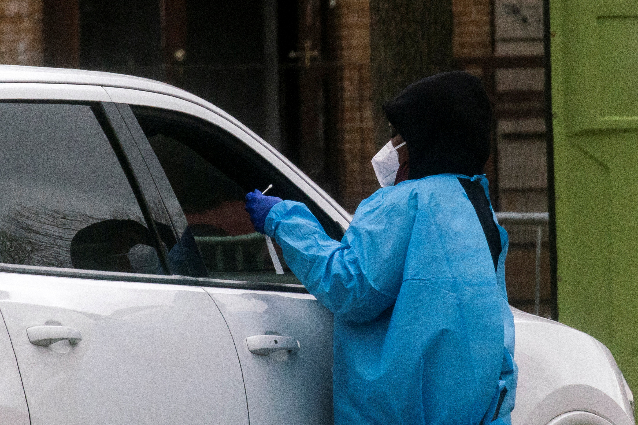 A health worker does a coronavirus disease (COVID-19) test as people wait at a drive-through COVID-19 testing center in a local street, in Newark, New Jersey, U.S., April 2, 2021. REUTERS/Eduardo Munoz
