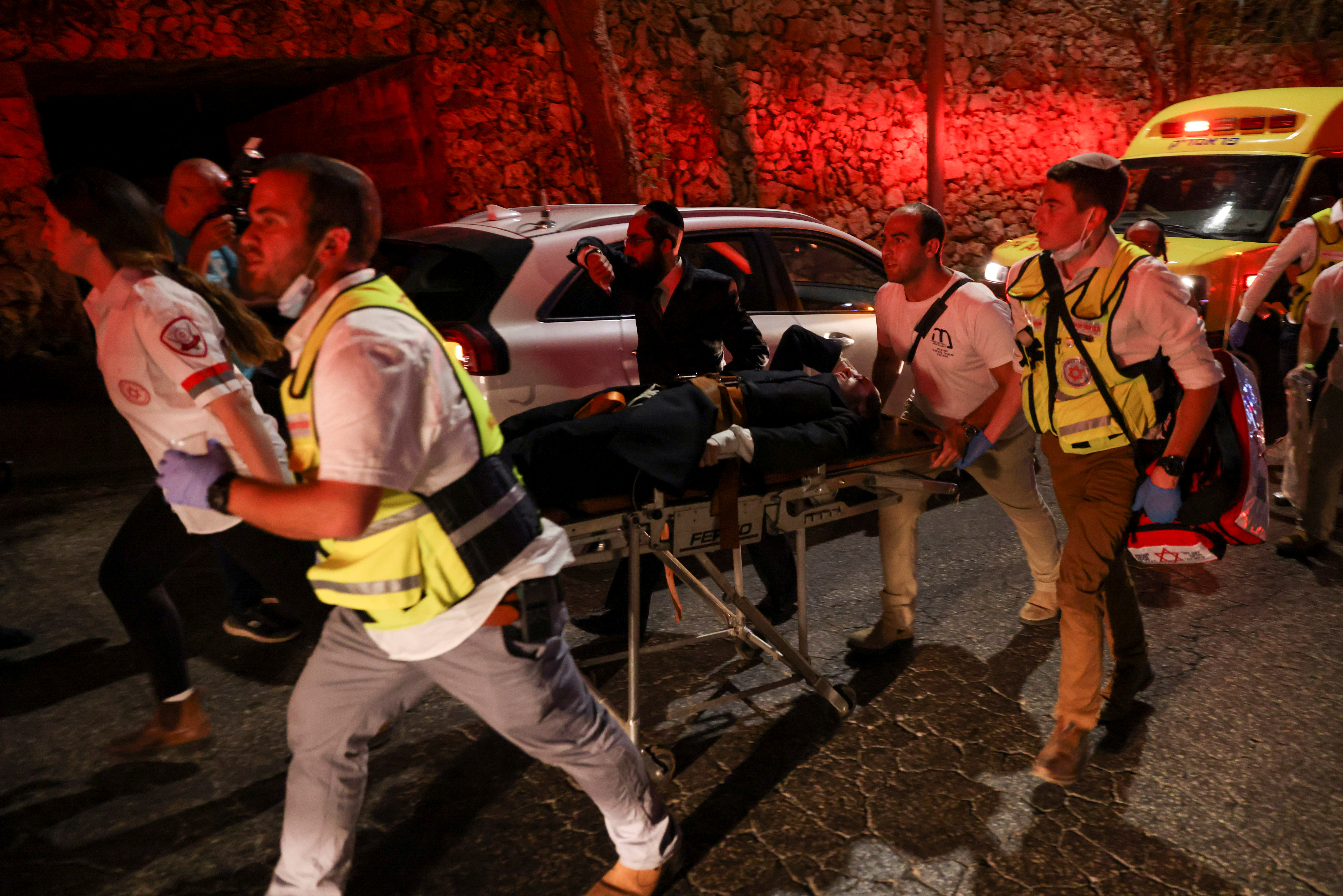 Rescue workers transport on a stretcher injured people outside a synagogue where a grandstand collapsed during a religious celebration in Givat Zeev, in the occupied West Bank, May 16, 2021. REUTERS/Ronen Zvulun