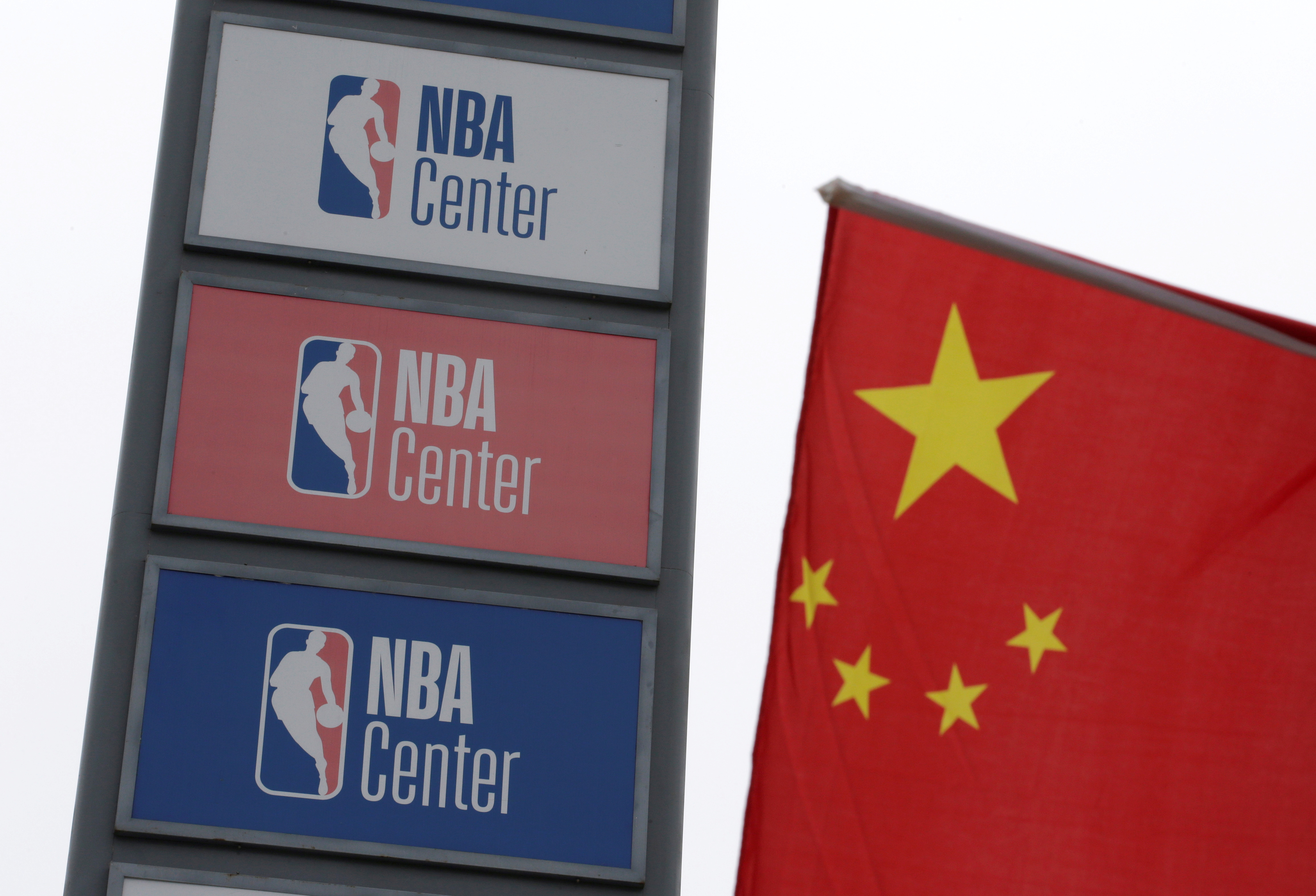 NBA logos are seen next to a Chinese national flag outside a NBA-themed lifestyle complex on the outskirts of Tianjin, China, October 10, 2019. REUTERS/Jason Lee/File Photo