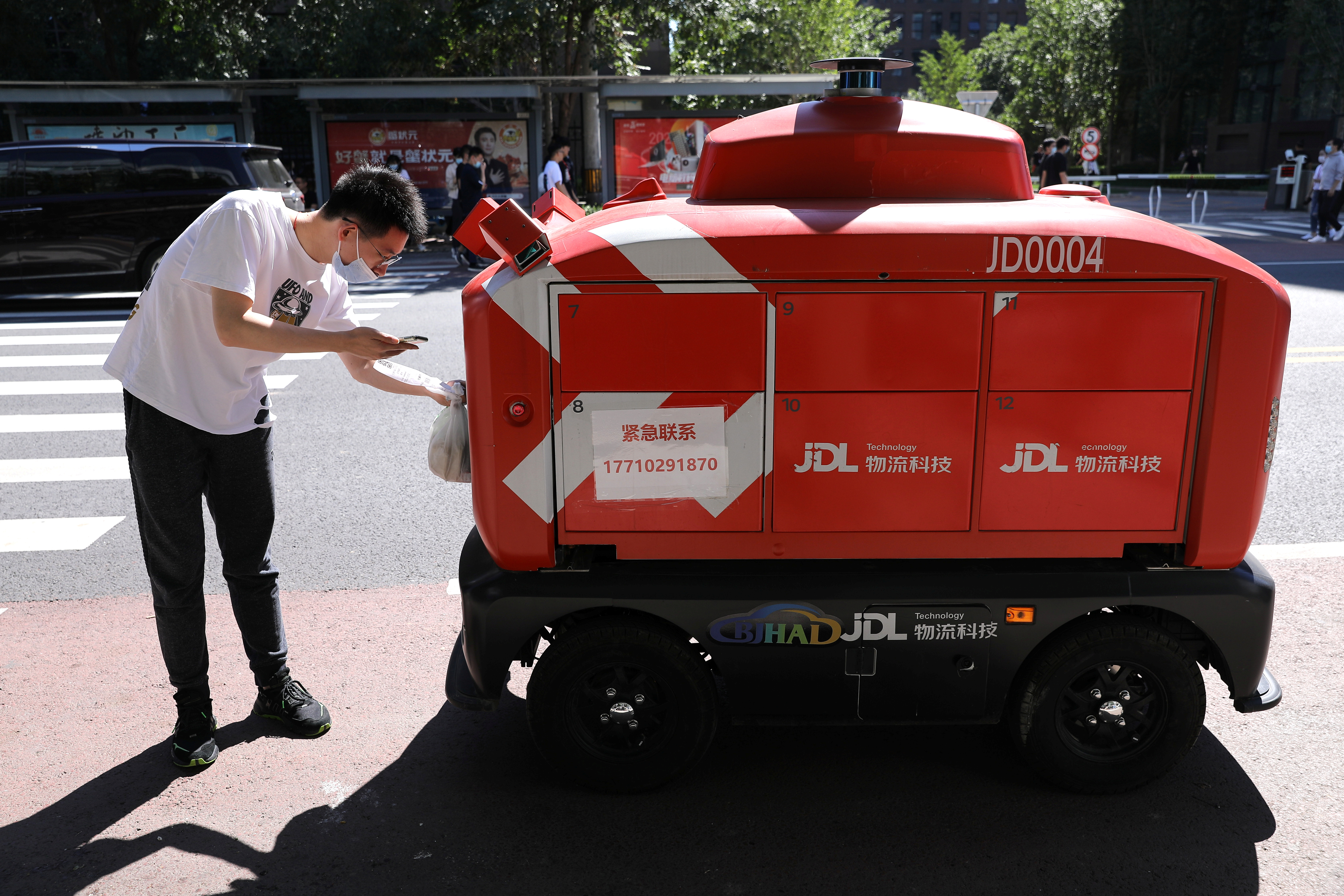 A person inputs a code on a screen of an autonomous delivery vehicle by JD Logistics, the delivery arm of JD.com, as he tries to pick up goods, in Beijing, China September 22, 2021. Picture taken September 22, 2021. REUTERS/Tingshu Wang