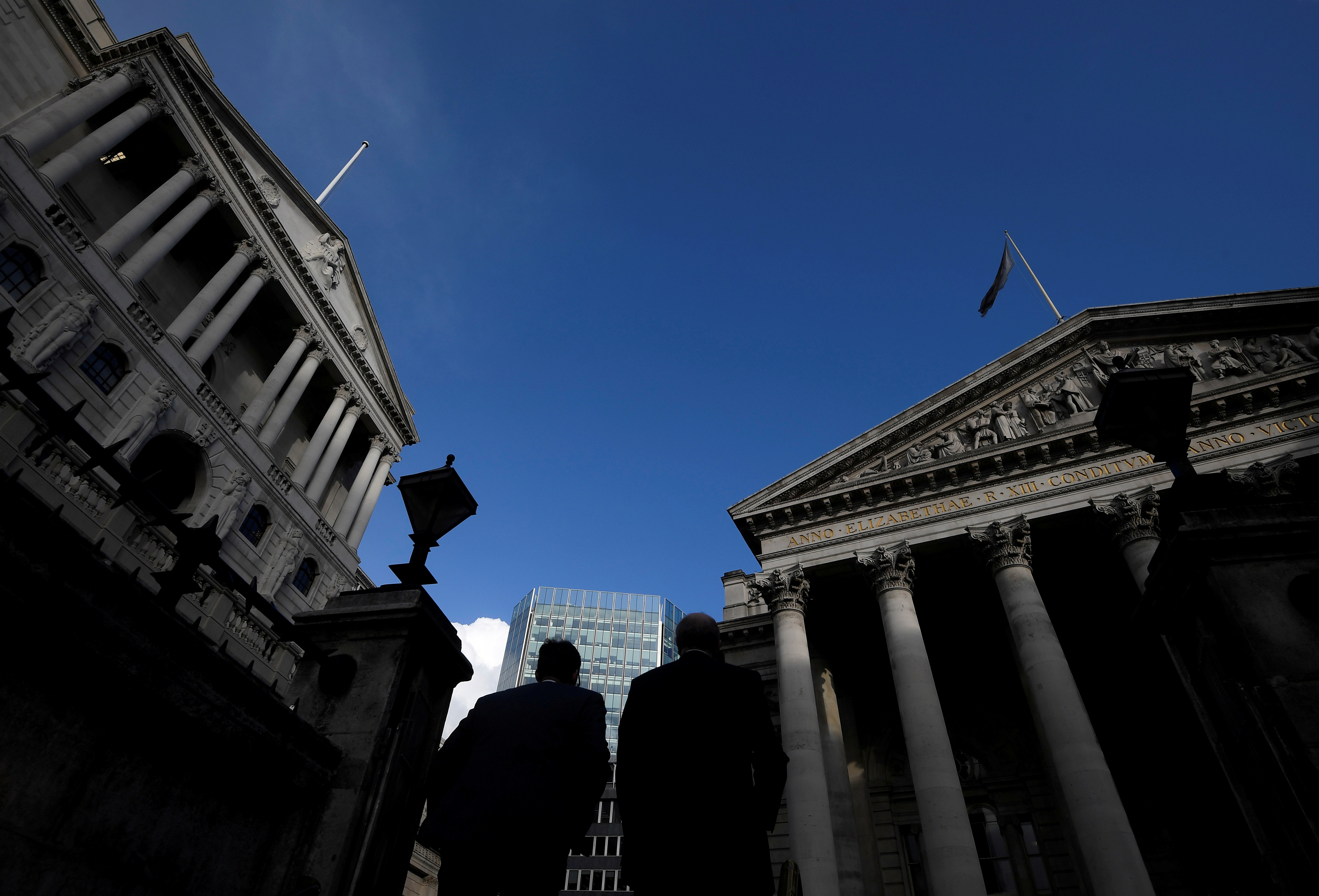 Workers emerge from Bank underground station with the Bank of England (L) and Royal Exchange building (R) seen in the City of London financial district, London, Britain, January 25, 2018. Picture taken January 25, 2018.   REUTERS/Toby Melville/File Photo