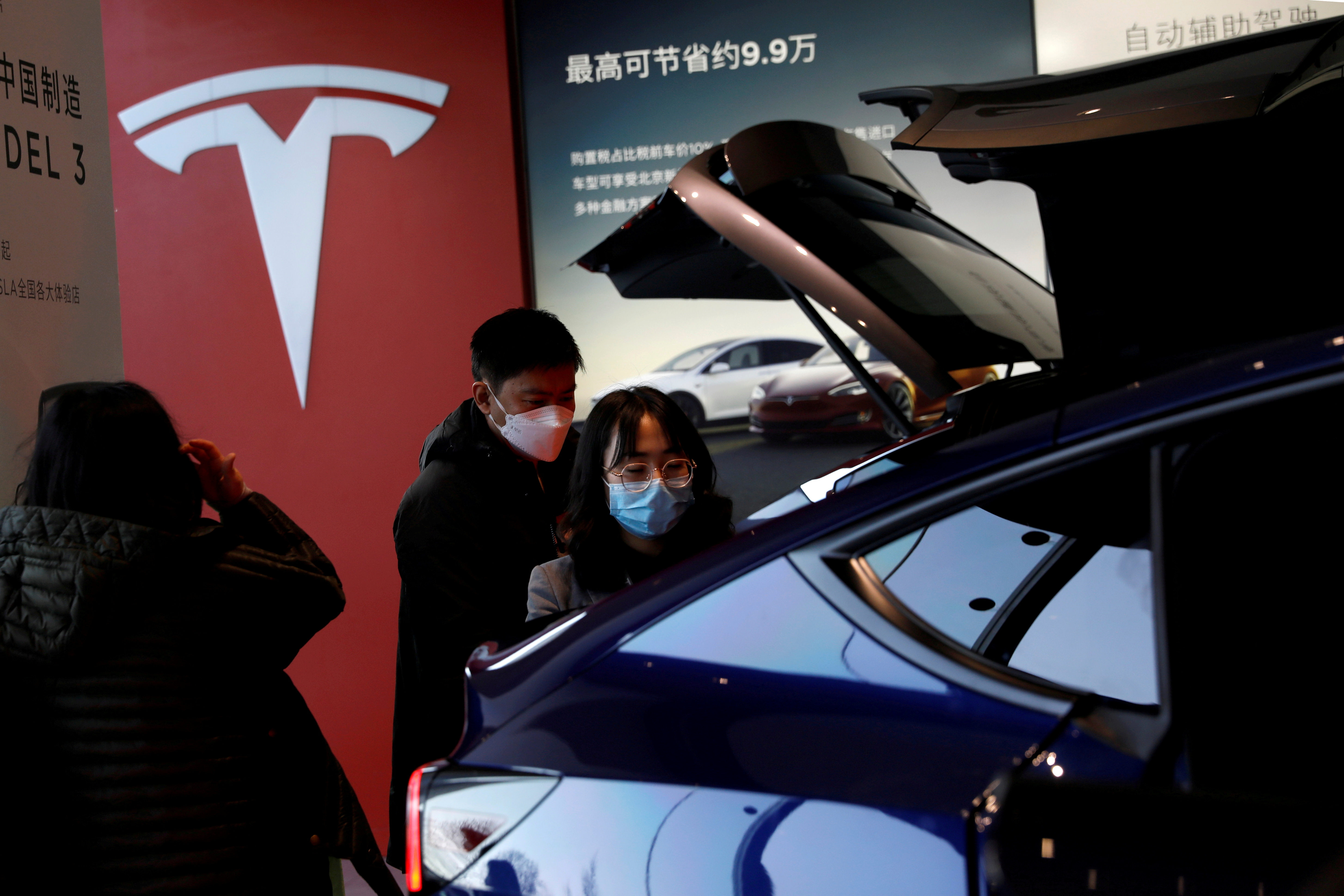 Visitors wearing face masks check a China-made Tesla Model Y sport utility vehicle (SUV) at the electric vehicle maker's showroom in Beijing, China January 5, 2021. REUTERS/Tingshu Wang