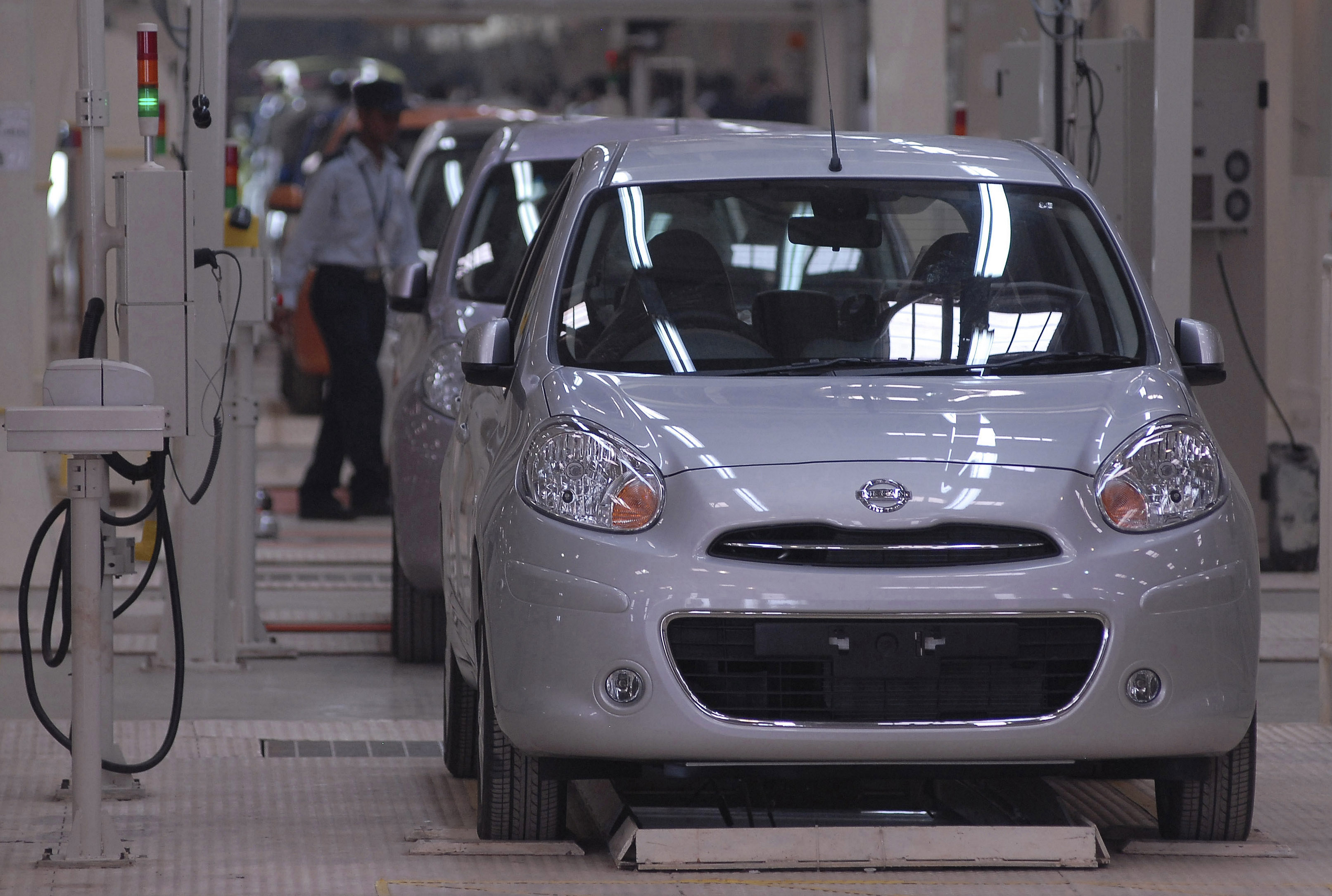 A security guard walks past 'Micra' cars lined at the newly-inaugurated Renault-Nissan Alliance auto plant in the southern Indian city of Chennai March 17, 2010. REUTERS/Babu