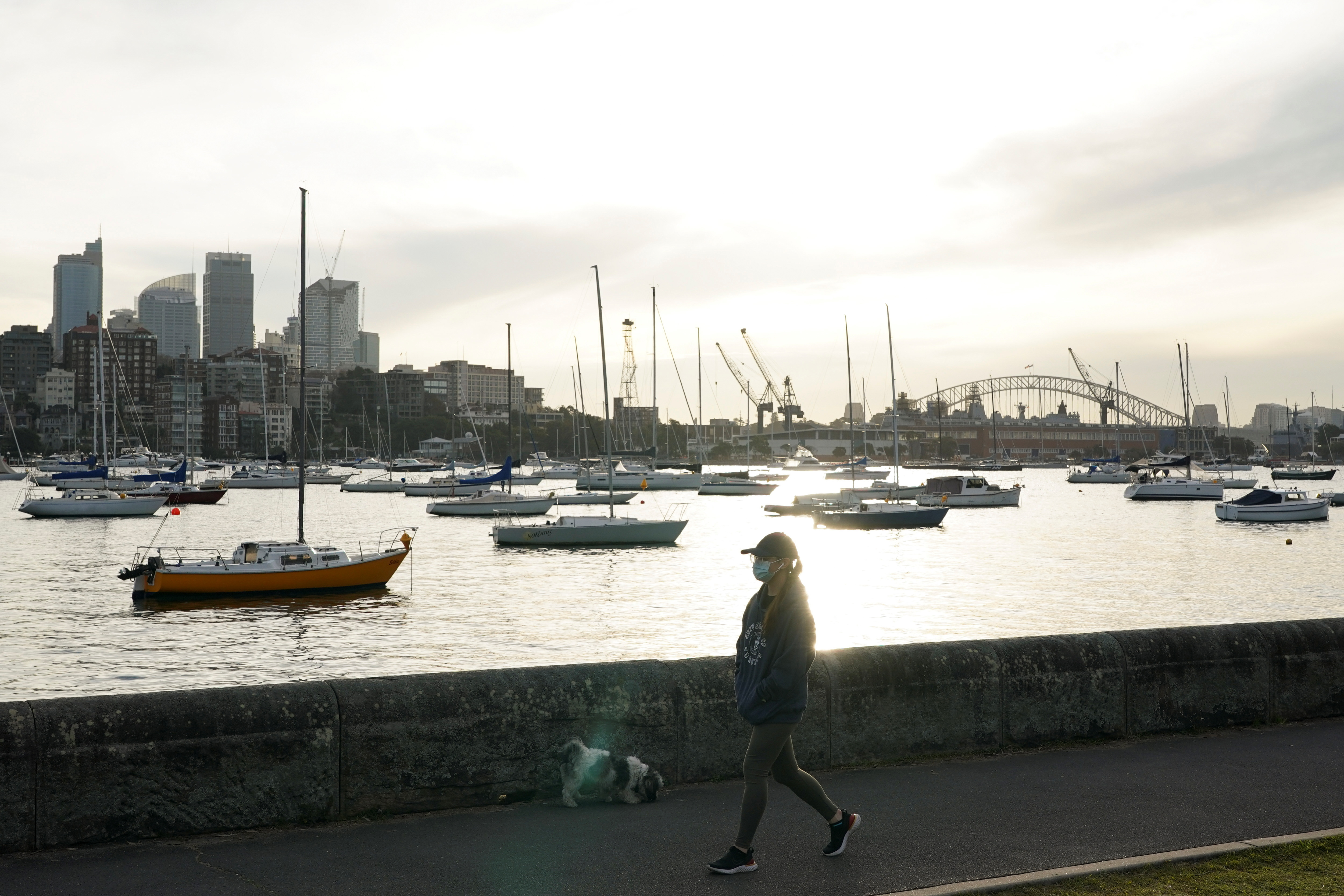 A woman wearing a protective face mask walks along a path by the water during a lockdown to slow the spread of a coronavirus disease (COVID-19) in Sydney, Australia, July 8, 2021. REUTERS / Loren Elliott