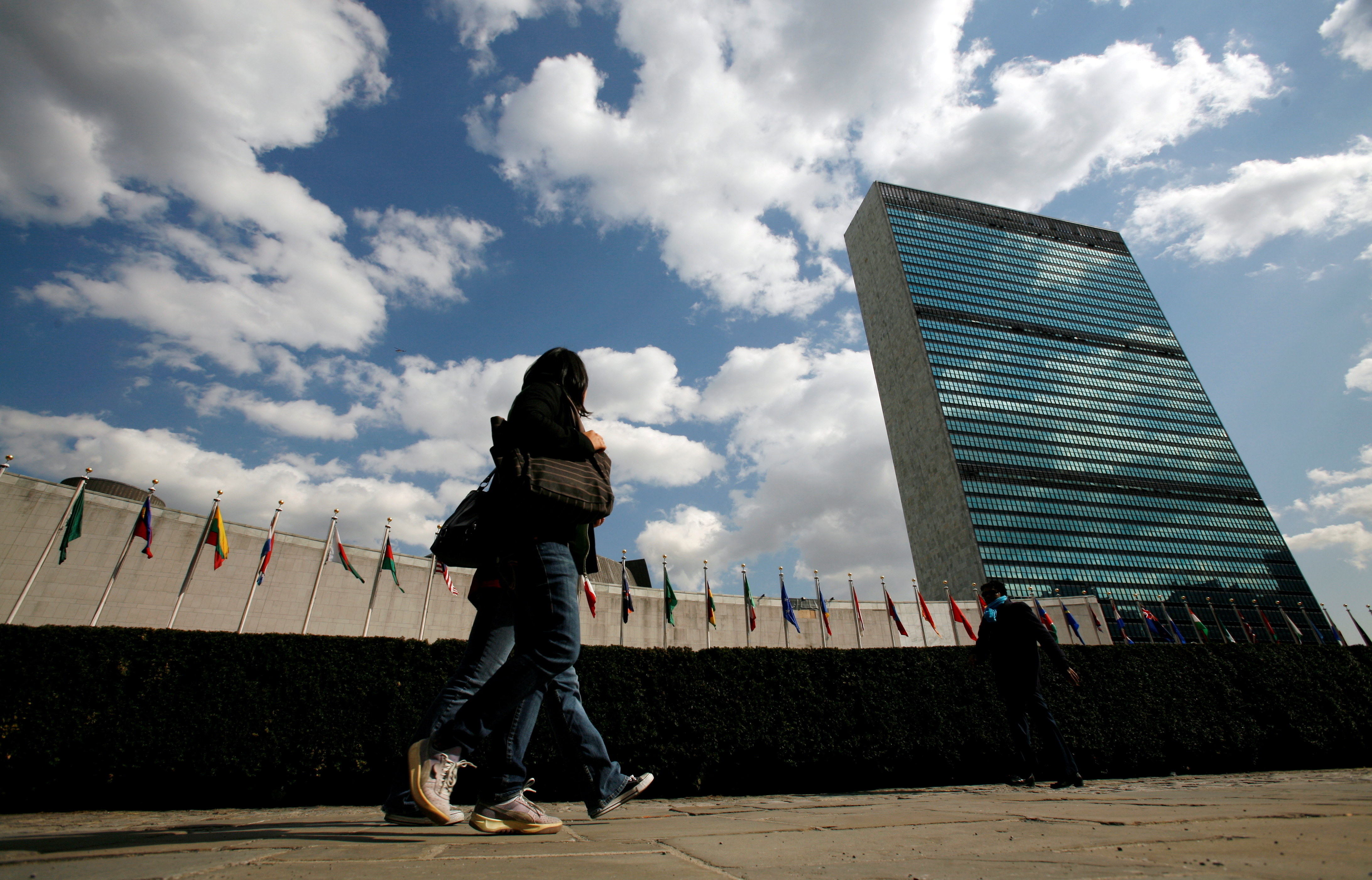 Tourists walk past the United Nations Headquarters in New York, March 24, 2008. At left is the U.N. General Assembly building and at right is the U.N. Secretariat building. REUTERS/Mike Segar